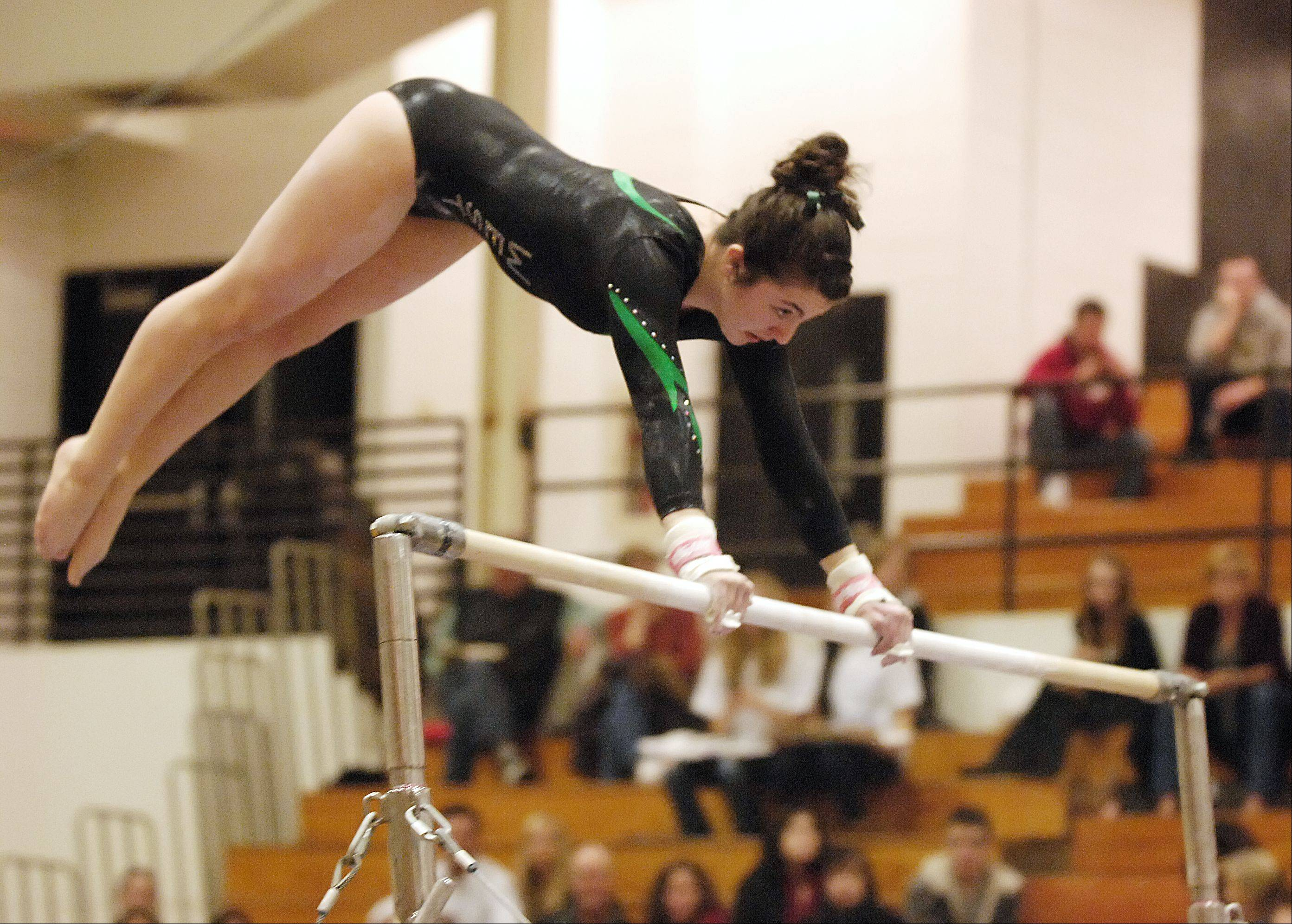 Mark Black/mblack@dailyherald.comMissy Guzman of Glenbard West performs on the bars during the girls gymnastics gectional tournament at Glenbard North High School.