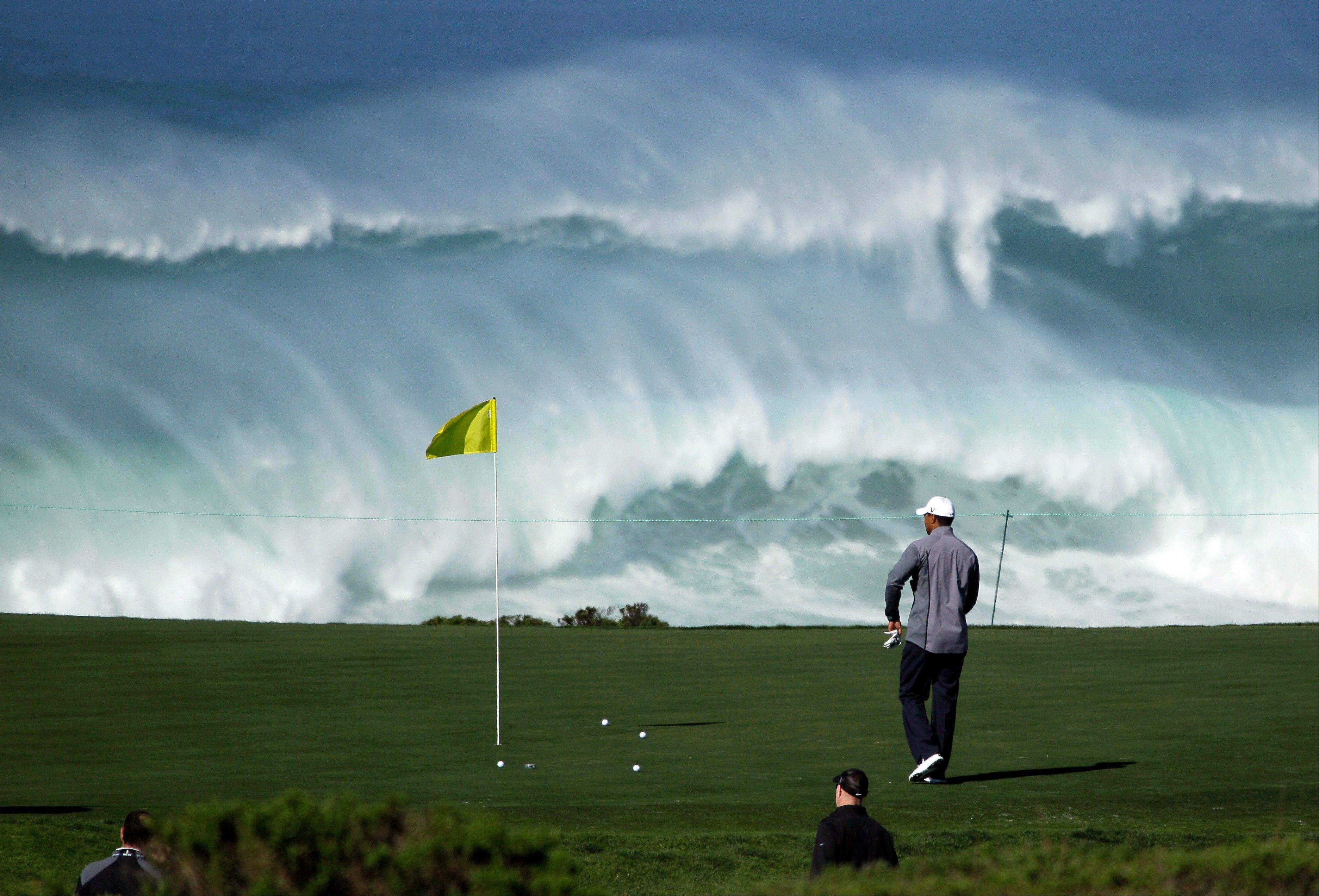 Tiger Woods walks to his ball on the 15th green of the Monterey Peninsula Country Club shore course Wednesday as waves crash in the background during a practice round at the AT&T Pebble Beach National Pro-Am PGA Tour golf tournament.