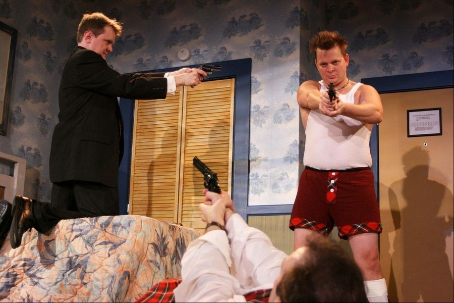 "Security agent Frank (Raymond Fox, left) gets in a stand off with an eccentric hit man (Joe Foust, right) and police detective Eric Sheridan (Kevin McKillip, on the floor) in First Folio Theatre's Chicago-area premiere of Paul Slade Smith's comedy ""Unnecessary Farce"" at Mayslake Peabody Estate in Oak Brook."