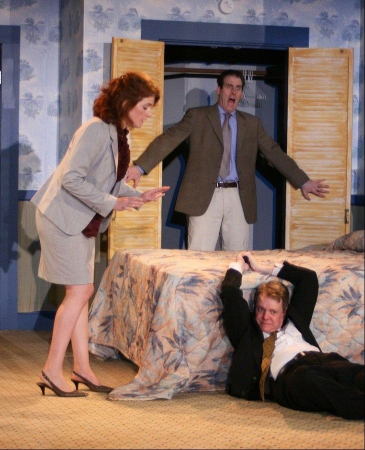 "Security agent Frank (Raymond Fox, right) aims his pistol at police detective Eric Sheridan (Kevin McKillip, center) as the accountant Karen Brown (Molly Glynn, left) looks on in First Folio Theatre's Chicago-area premiere of Paul Slade Smith's comedy ""Unnecessary Farce"" at Mayslake Peabody Estate in Oak Brook."
