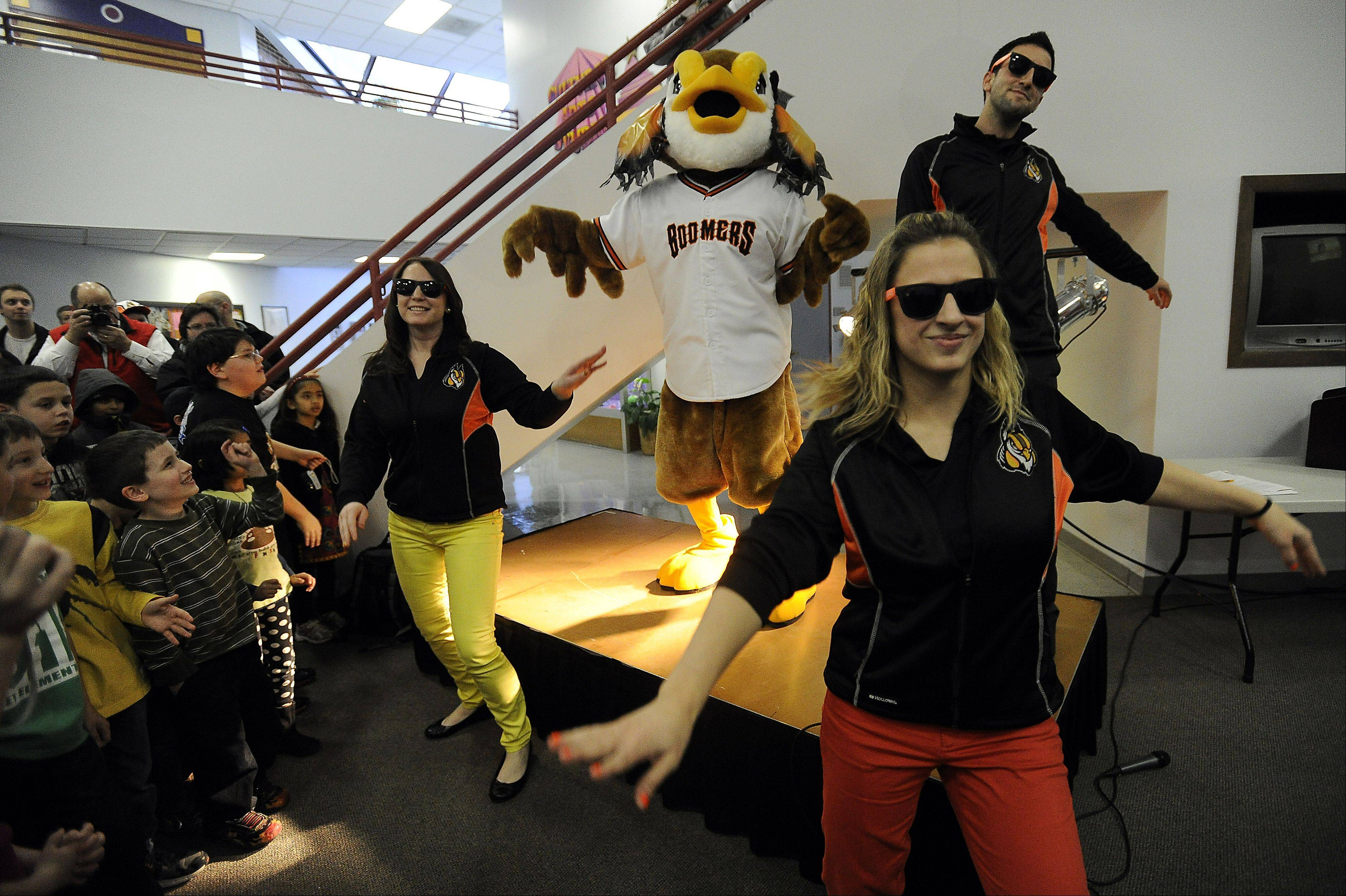 Carly Salczynski, Sara Ronano and Andy Viano, general manager and president of the Schaumburg Boomers, dance along with Coop at the unveiling Thursday.