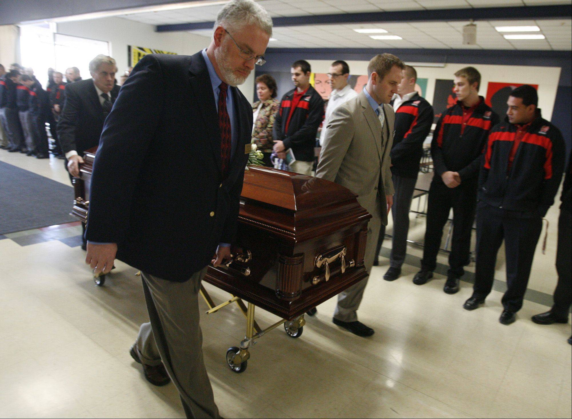 North Central College football players line up as the casket of Shaun Wild is brought into Brown Deer High School for the memorial service.