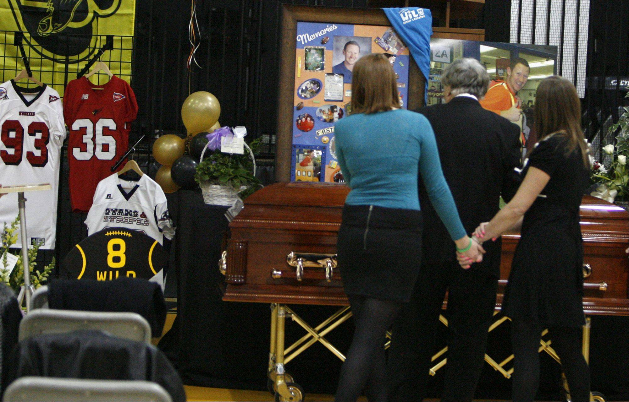 Shannon Wild, left, views the casket and photographs of her brother Shaun Wild.