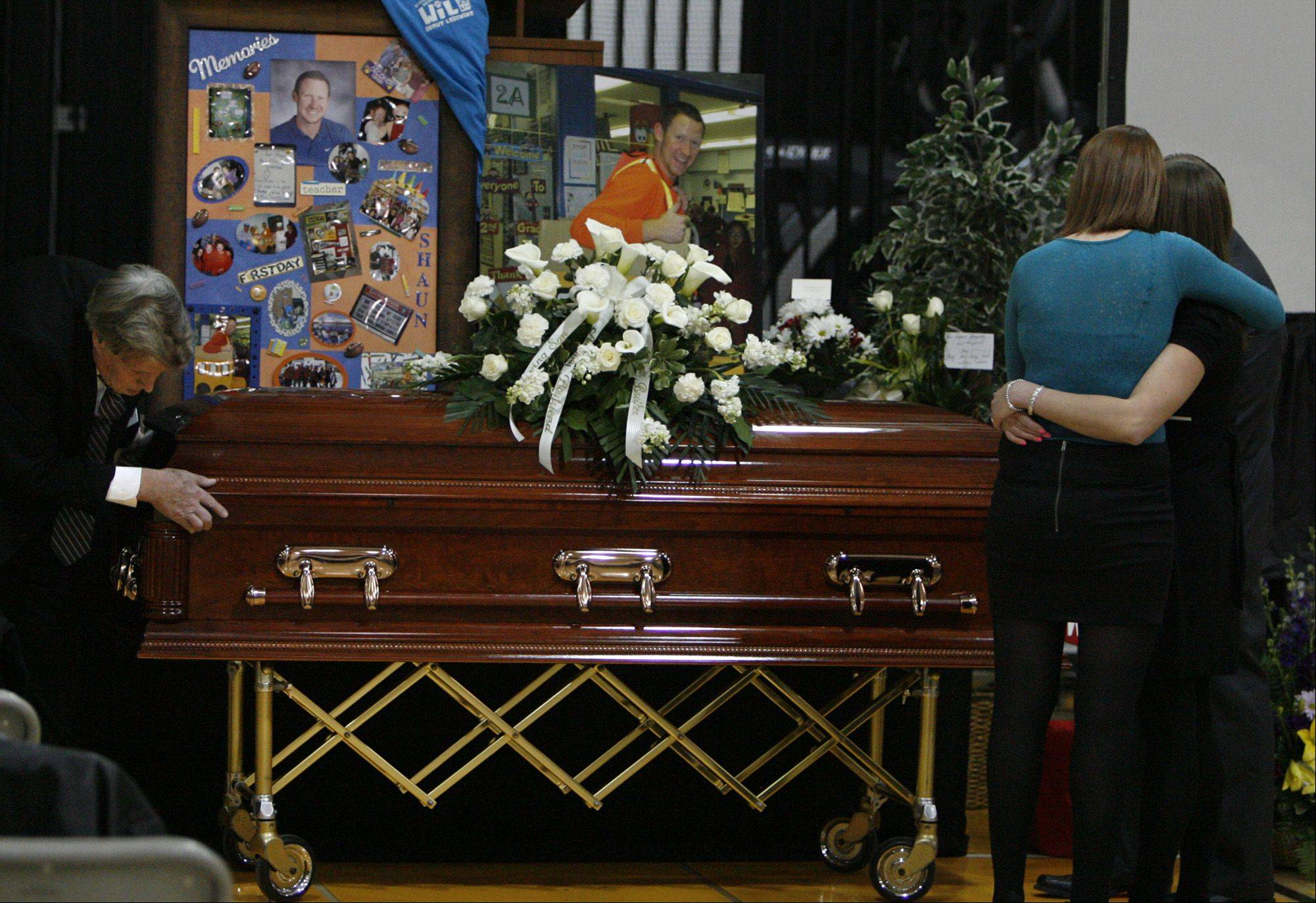 Shannon Wild, left, receives a hug as she views the casket and photographs of her brother Shaun Wild during the visitation for the slain Naperville teacher.