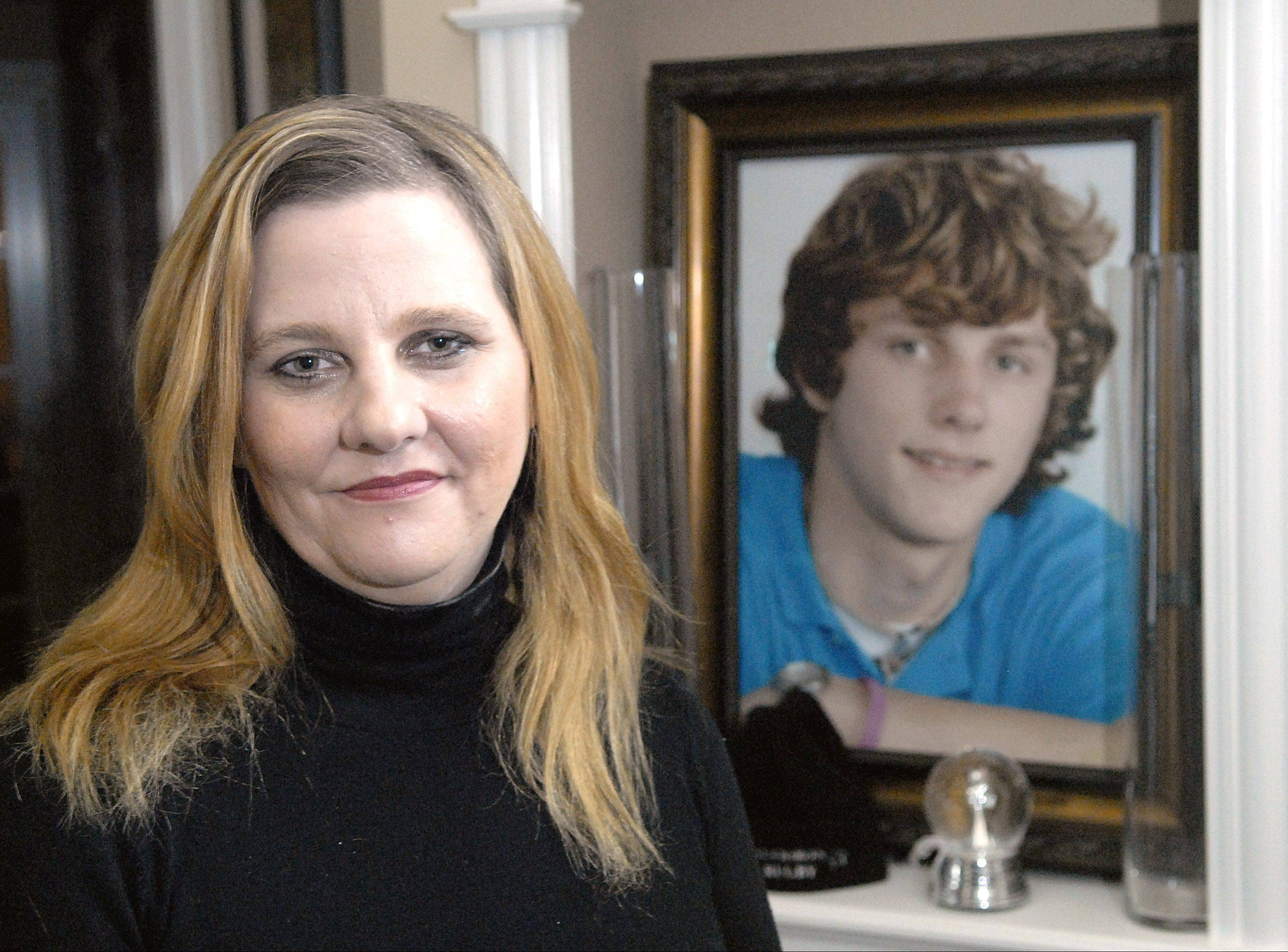 Mary Godee sits by a senior portrait of her late son, Cameron, in her Elburn home. Cameron, a 2009 St. Charles East High School graduate, was killed in a drunken driving crash. The driver, Onofrio Lorusso, of Wayne, violated his probation for the fatal DUI and got sentenced to 30 days in jail Thursday. Mary Godee and prosecutors wanted prison time. Kane County Judge Timothy Sheldon also said Godee sent him a threatening letter, which she denies, and she said she plans to file a complaint against him.