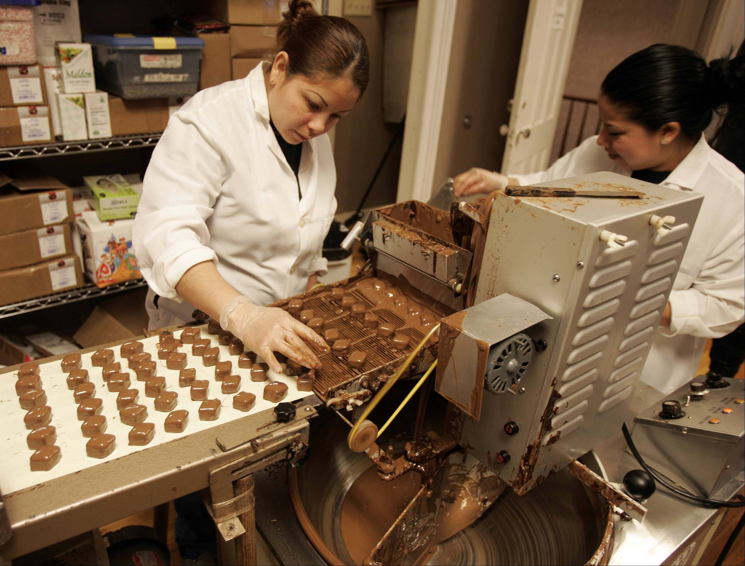 Mireya Ojeda, left, puts the swirl on the top of some peanut butter diamonds at Graham's Fine Chocolates and Ice Cream in Geneva. The staff can tell what is in the candy by looking at the swirl, which is different for each type of candy.