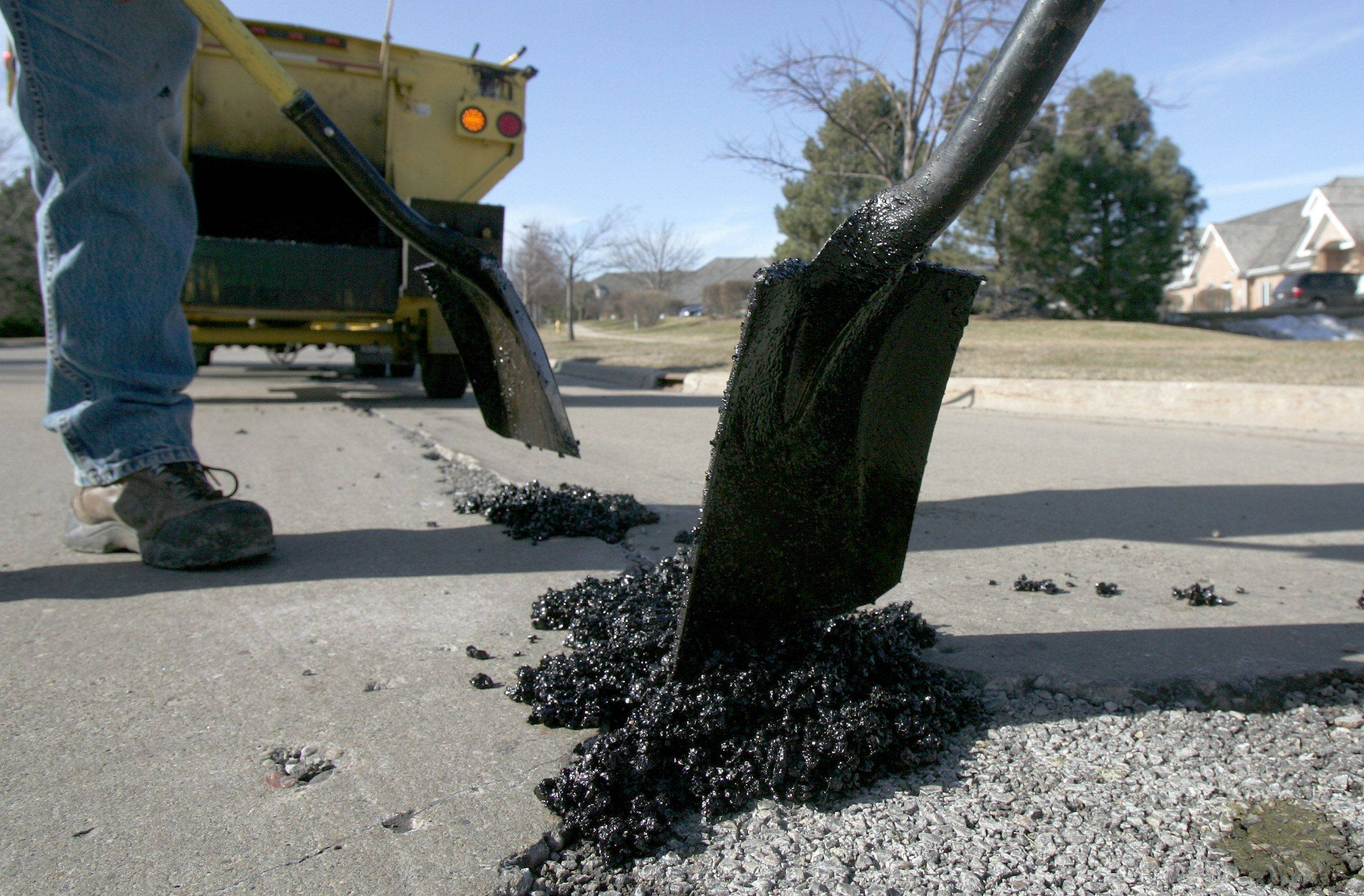 Crews repair potholes on Florsheim Drive in Libertyville. The village is seeking voter approval to issue bonds for an extensive road repair program.