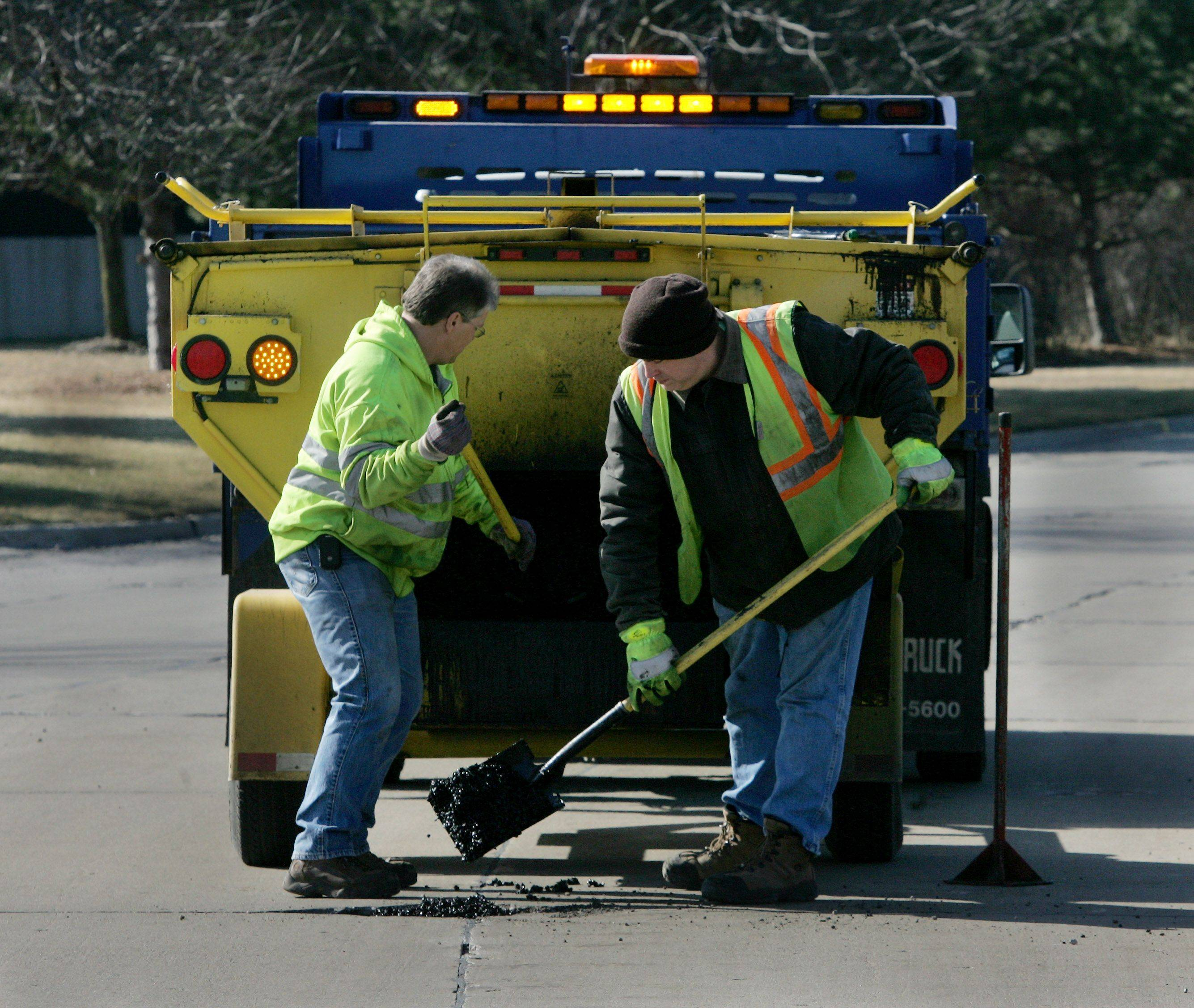 Libertyville public works employees Jeff Goodrich, left, and Jeff Lambert repair potholes on Florsheim Drive in Libertyville. The village is seeking voter approval to issue $20 million in bonds to repair and resurface about 30 miles of streets.