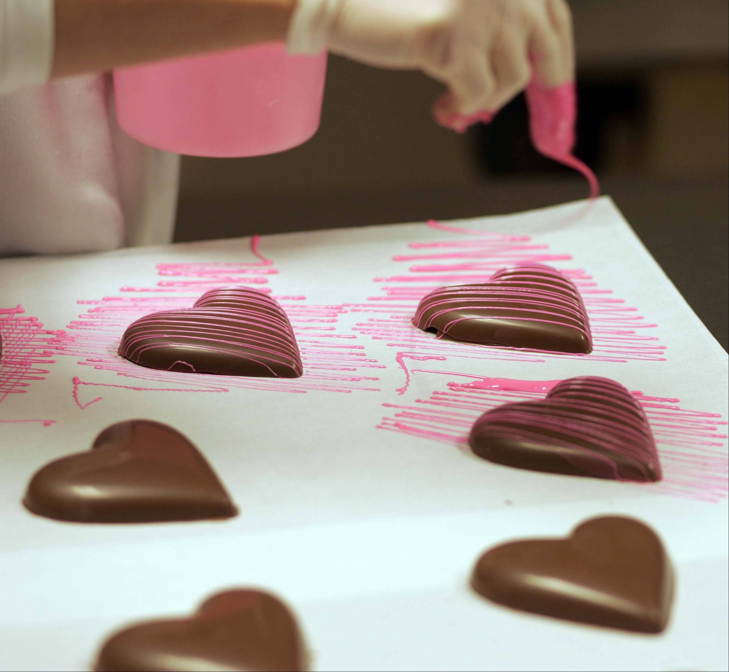 Pink chocolate is drizzled over what will be chocolate boxes at Graham's Fine Chocolates and Ice Cream in Geneva.