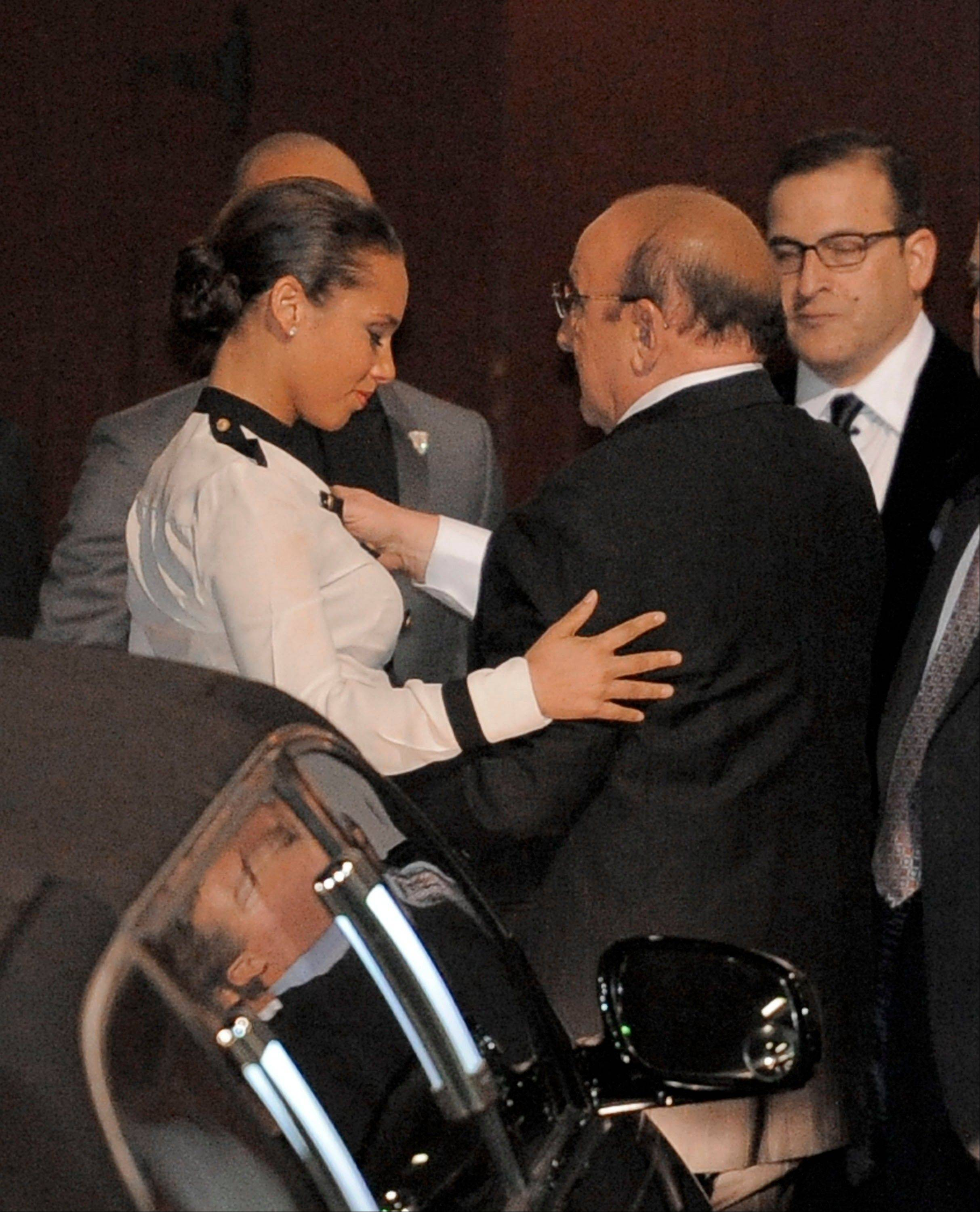 Alicia Keys, left, hugs Clive Davis at the loading dock Saturday outside the Beverly Hilton Hotel Saturday in Beverly Hills, Calif. Whitney Houston, who ruled as pop music's queen until her majestic voice and regal image were ravaged by drug use, erratic behavior and a tumultuous marriage to singer Bobby Brown, died Saturday. She was 48.
