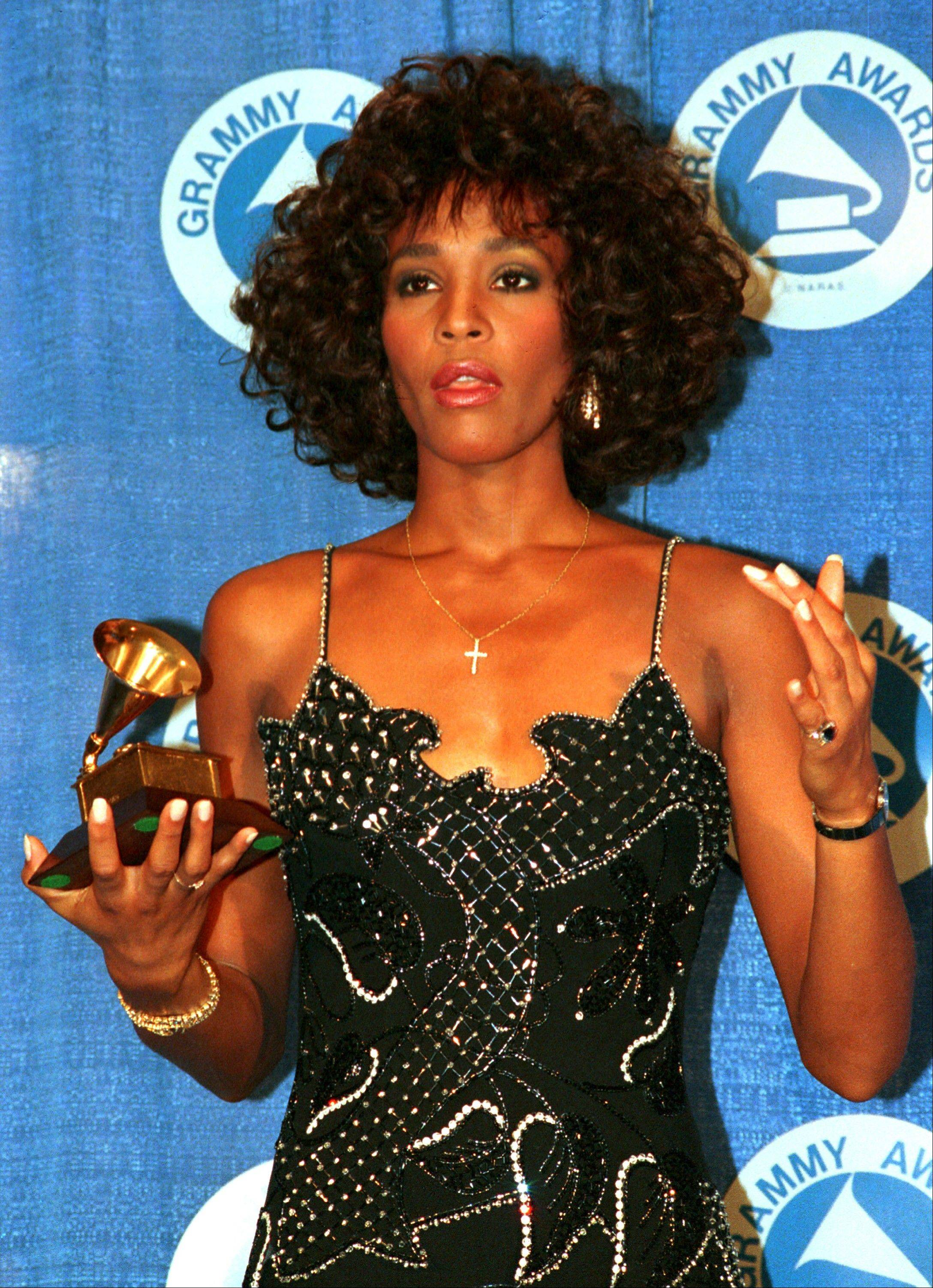 In this March 3, 1988, file photo, Whitney Houston poses with her Grammy at the annual Grammy Awards presentation in New York.