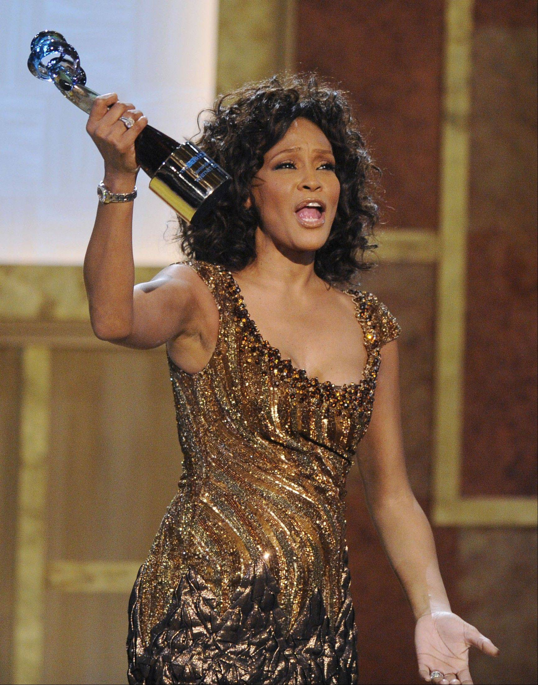 In this Saturday, Jan. 16, 2010, file photo, Whitney Houston accepts an award at the Warner Theatre during the 2010 BET Hip Hop Honors in Washington.