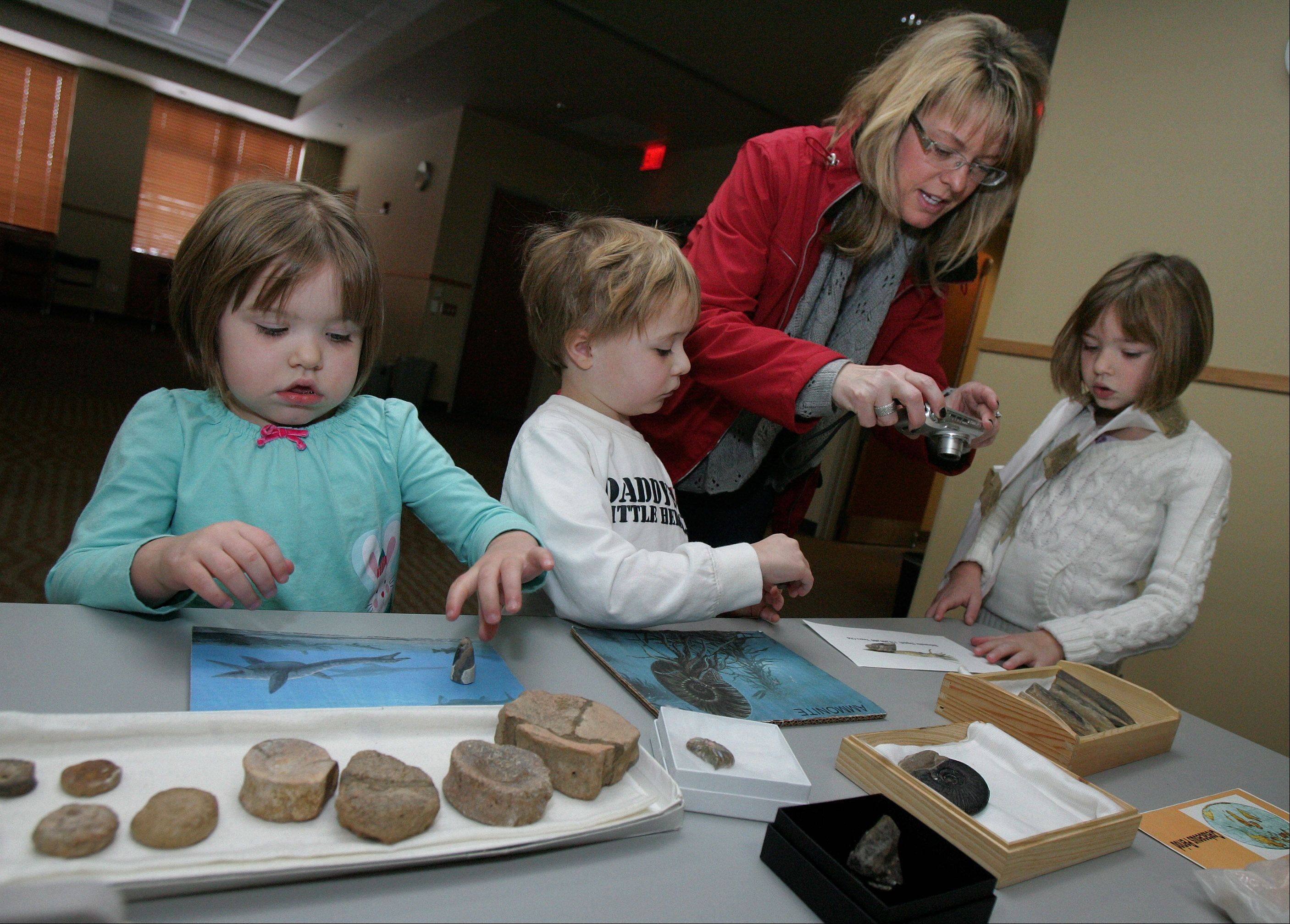 "Long Grove residents Erin Mondrowski with her children Maisie, 3, Matthew, 4, and Molly, 7, look at fauna and small water animal fossils during the ""Dinosauria"" program at the Ela Area Public Library in Lake Zurich. It was presented by dinosaur hunters Don Pfister and Lisa Zago-Martin."