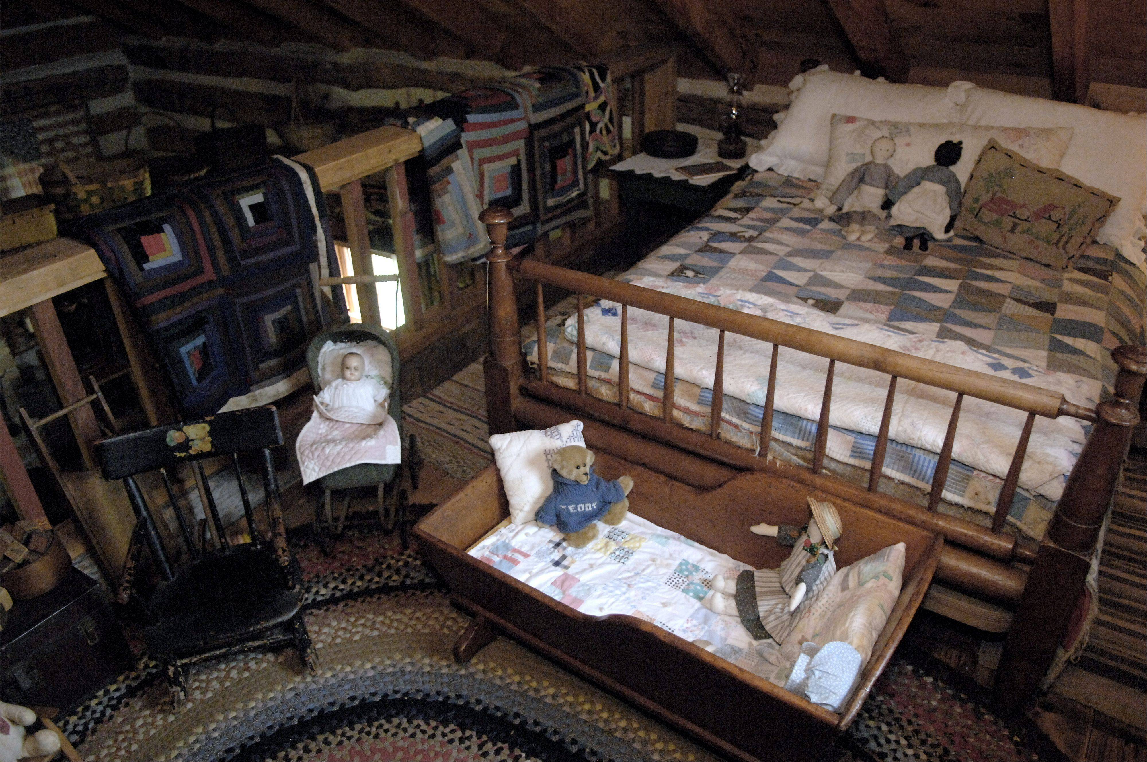The loft shows the quilts, dolls and beds that Mary Lou White collected for the 1840s log house. Some of the quilts are family heirlooms.