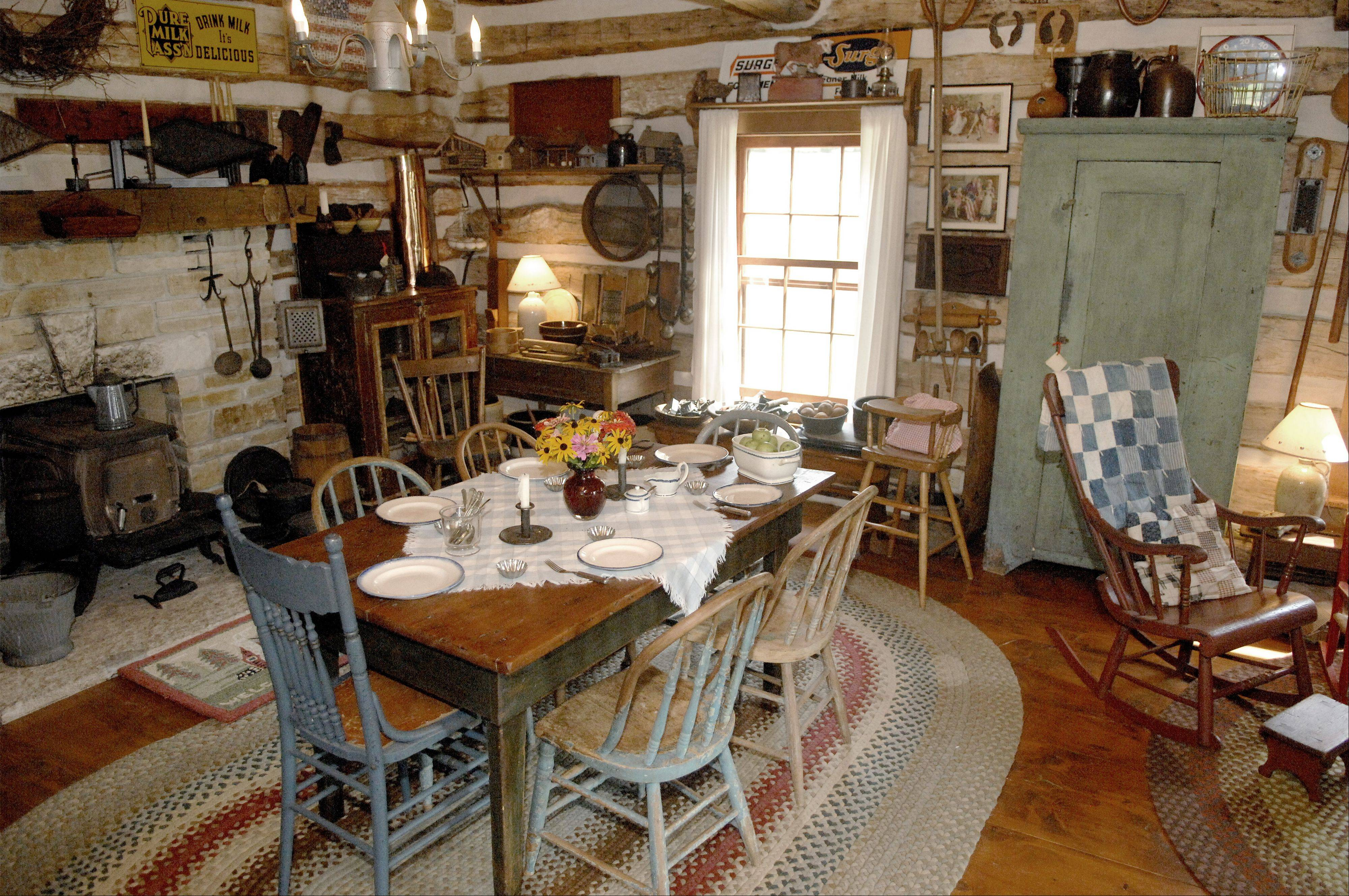 The furnishings in the old log house show what John White is talking about when he says the antiques he sells are farm primitives. The green pine cupboard is priced at $2,350.