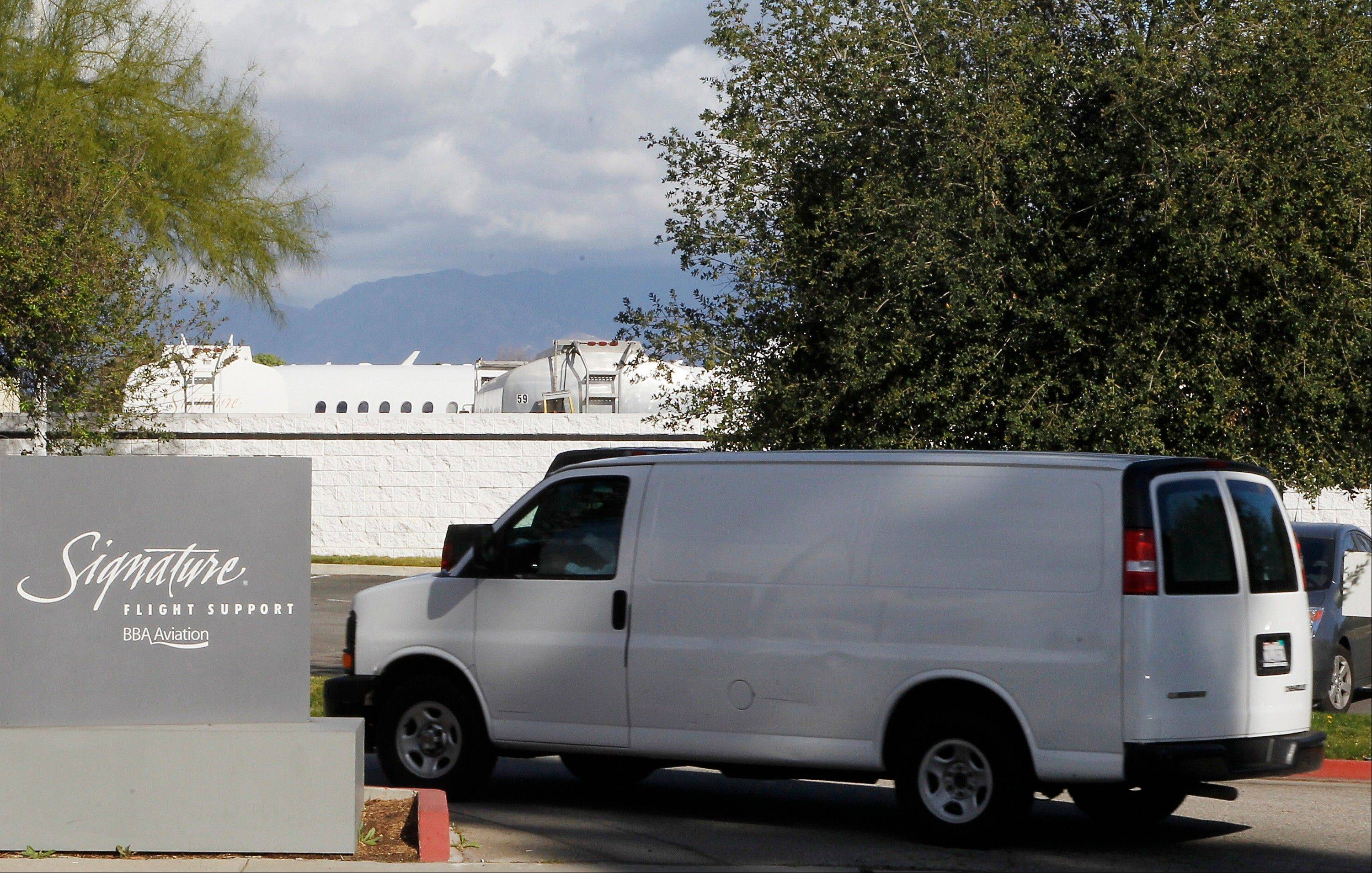 An unmarked van transports the body of singer Whitney Houston into the Van Nuys Airport in Van Nuys, Calif., Monday. The Los Angeles County coroner's office released the body to the family late Monday morning and it was flown to New Jersey, where her family was making arrangements for a funeral at the end of the week.