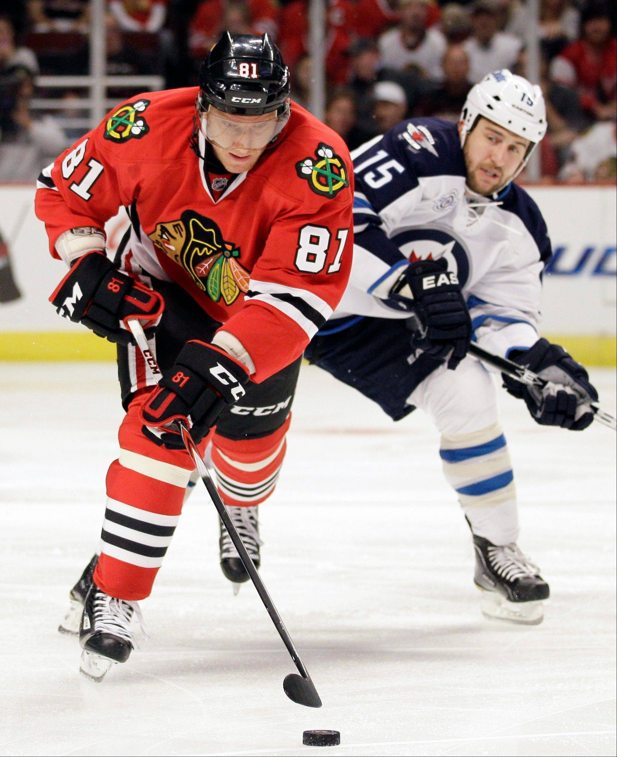 Marian Hossa, here controlling the puck past Winnipeg's Tanner Glass in October, has no points since the all-star break.