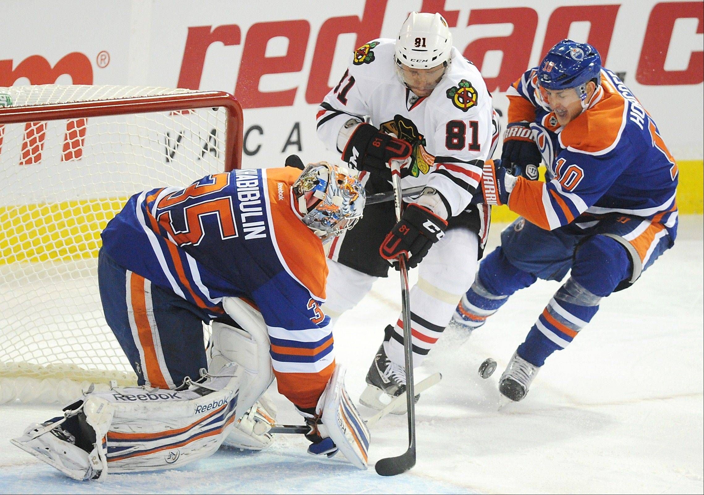 The Edmonton Oilers' Shawn Horcoff, right, defends goalie Nikolai Khabibulin, left, from the Chicago Blackhawks' Marian Hossa during first period NHL hockey action in Edmonton on Saturday, Nov. 19, 2011.
