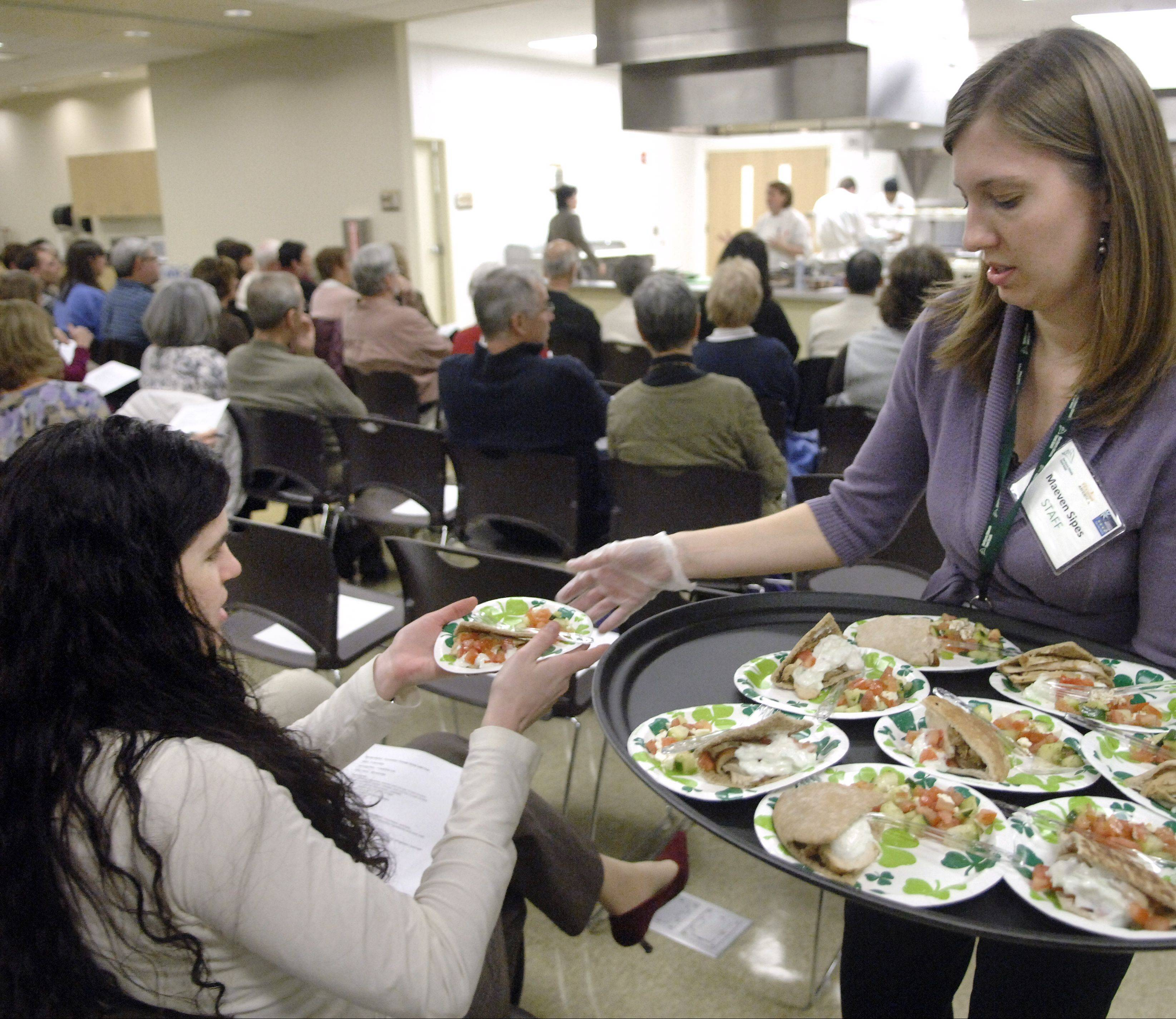 Staff member Maeven Sipes hands out samples of chicken gyros and a cucumber, tomato and feta salad while Jen Bucko Lamplough of Batavia demonstrates healthful cooking earlier this month at the Northern Illinois Food Bank in Geneva.