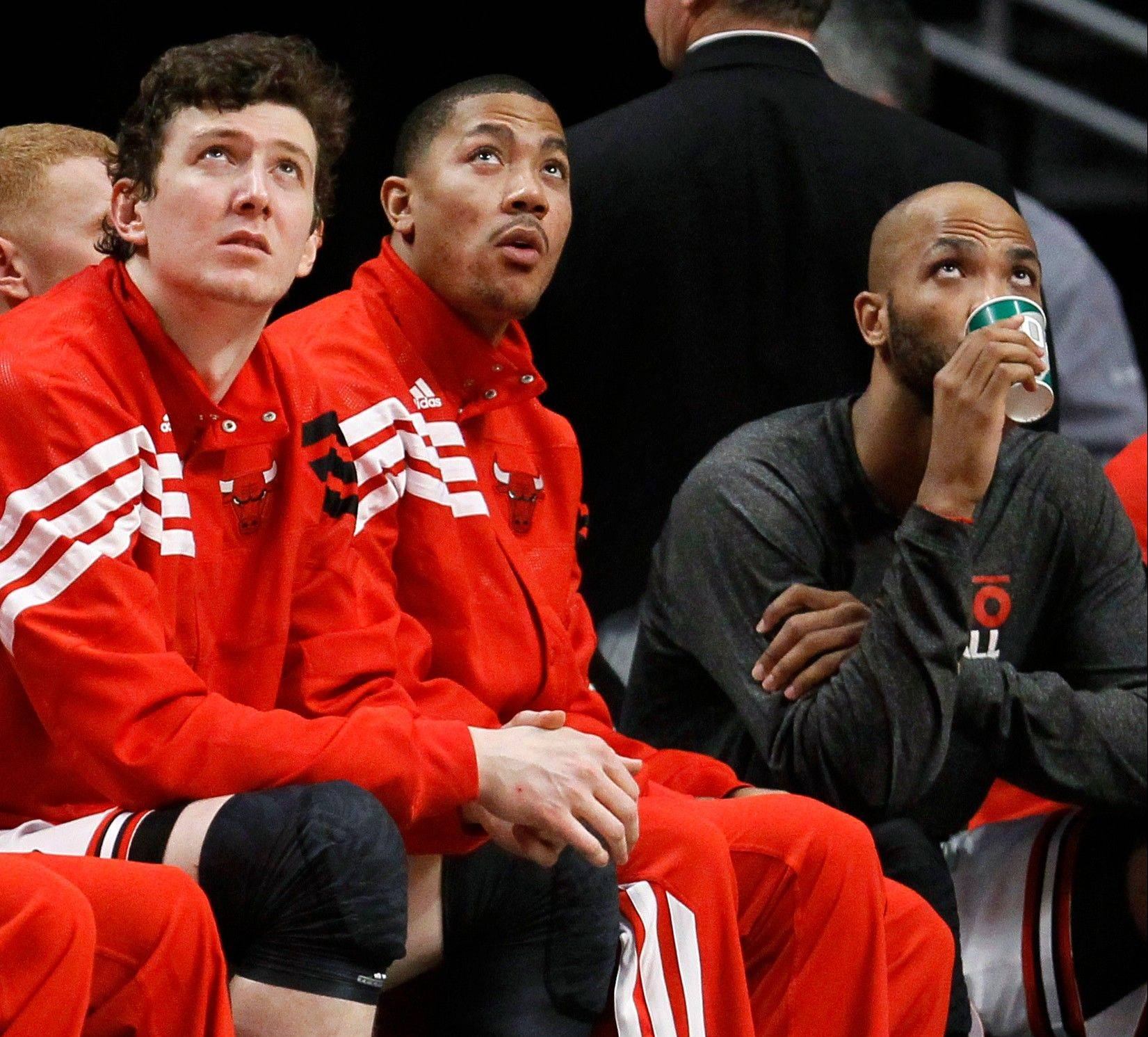Derrick Rose, center, was a spectator in the Bulls' 121-115 win over the Kings at the United Center. Rose insists that his back spasms won't persist.