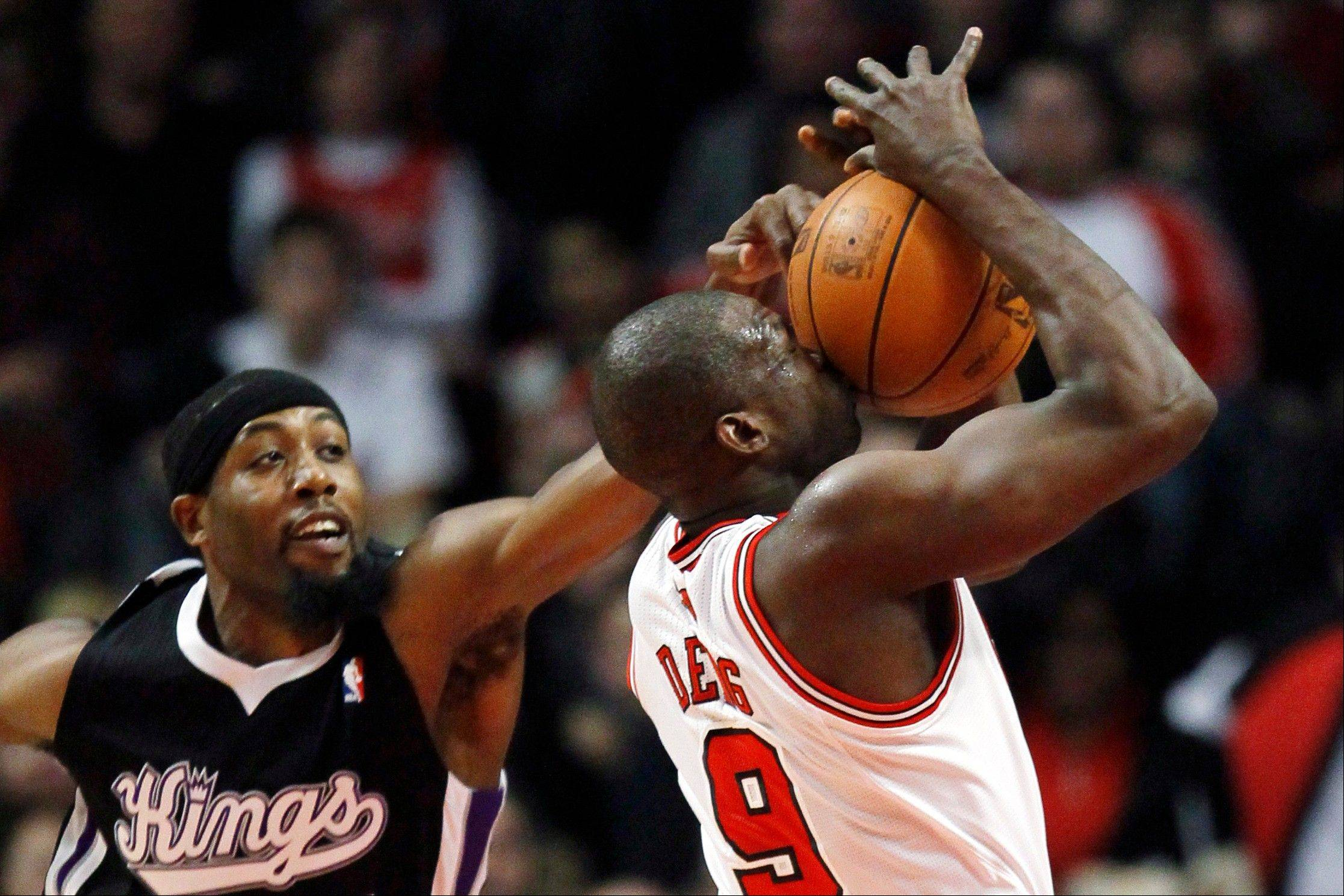 The Kings' John Salmons blocks a shot from the Bulls' Luol Deng on Tuesday at the United Center.