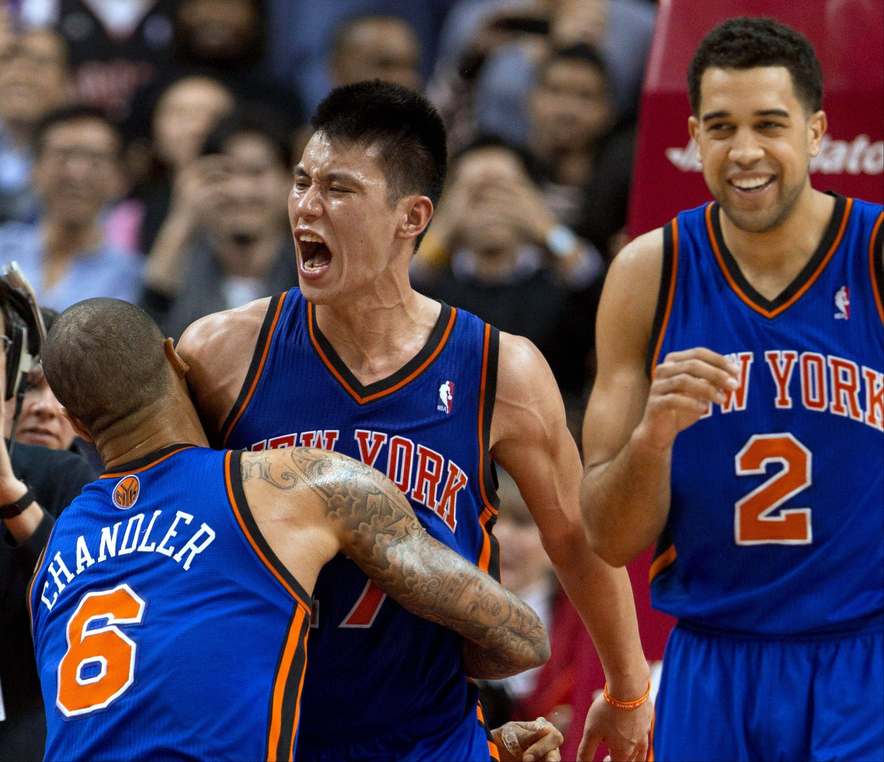 New York Knicks guard Jeremy Lin celebrates with teammates Tyson Chandler and Landry Fields after his game-winning 3-pointer Tuesday against the Toronto Raptors.