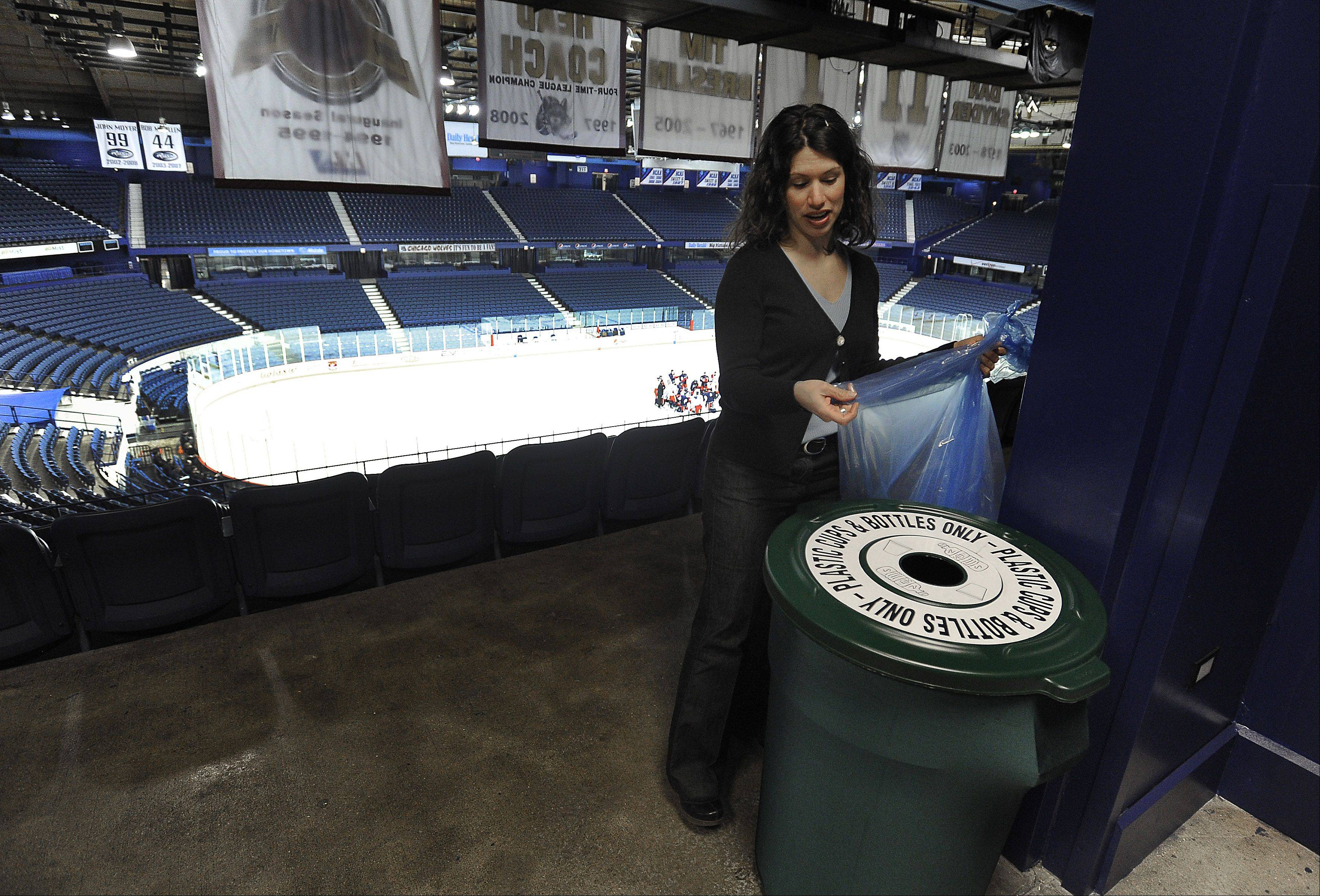 "Stephanie Katsaros, principal of Bright Beat, and sustainability manager at the Allstate Arena in Rosemont changes a blue bag in one of the waste bins. ""We increased the number of recycling bins, brought in a sponsor who helped with messaging and printing of posters,"" Katsaros said."