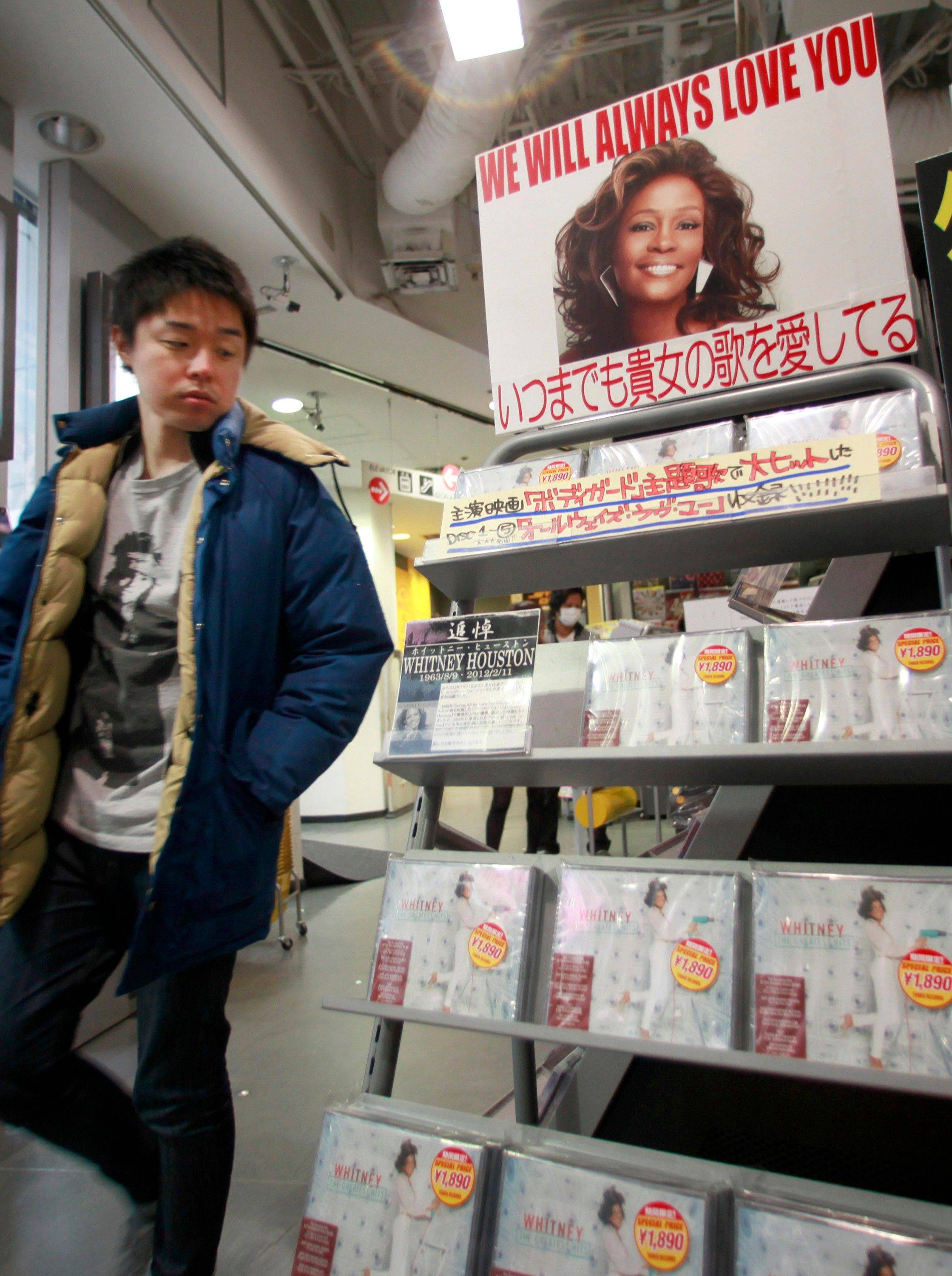 "A shopper looks at CDs on sale at the special corner set up for pop queen Whitney Houston, with a message ""We will always love you,"" at a music shop in Tokyo Tuesday, Feb. 14, 2012. Houston died Saturday, Feb. 11. she was 48."