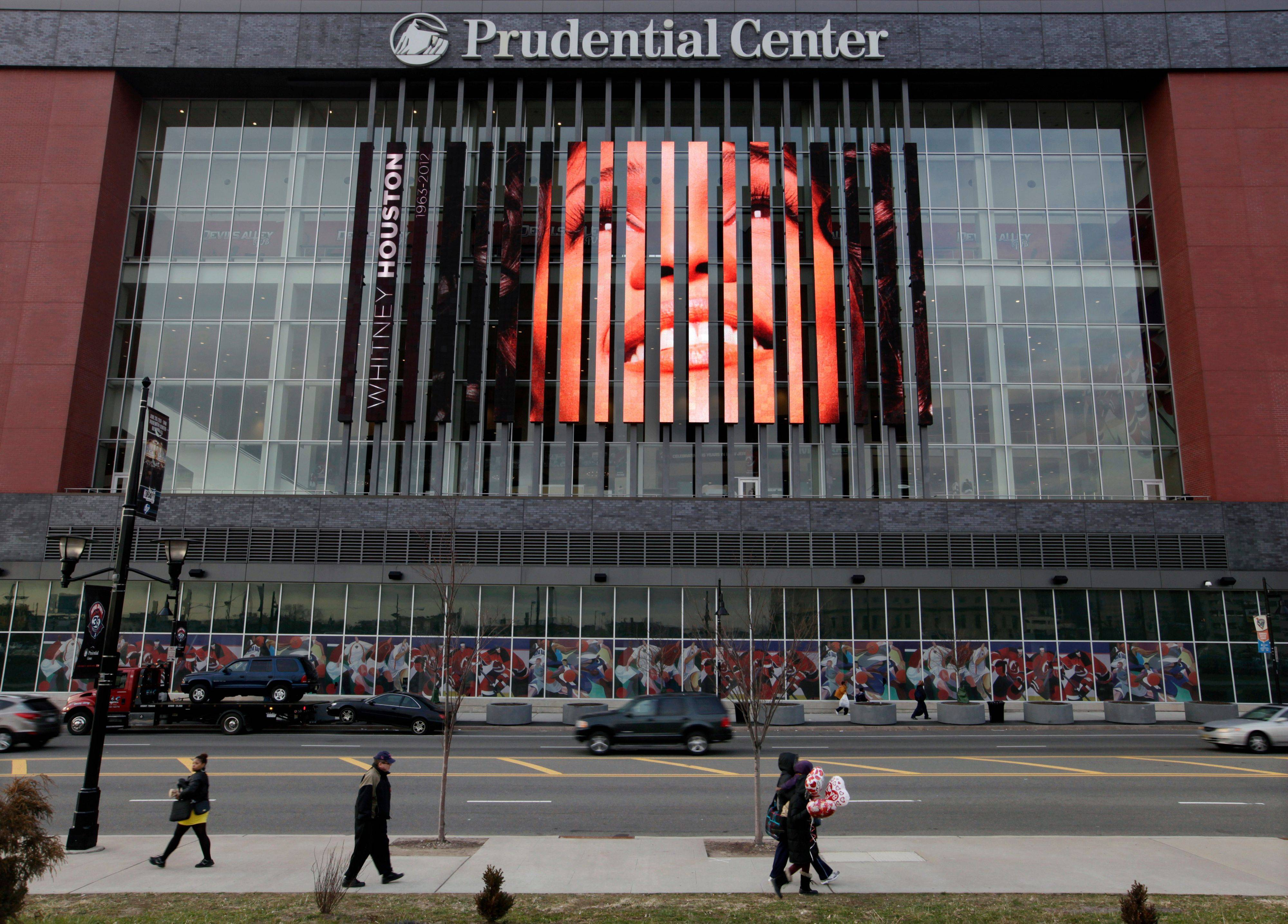 People walk past, a large image of Whitney Houston displayed on the side of the Prudential Center in Newark, N.J., Tuesday, Feb. 14, 2012. Houston's funeral will be held Saturday in the church where she first showcased her singing talents as a child, her family choosing to remember her in a private service rather than in a large event at an arena. Officials had discussed the possibility of holding a memorial at the Prudential Center, a major sports and entertainment venue that can seat about 18,000 people, but the funeral home said it had been ruled out. Houston, 48, died Feb. 11 at a hotel in Beverly Hills, Calif., just hours before she was set to perform at producer Clive Davis' pre-Grammy Awards bash.