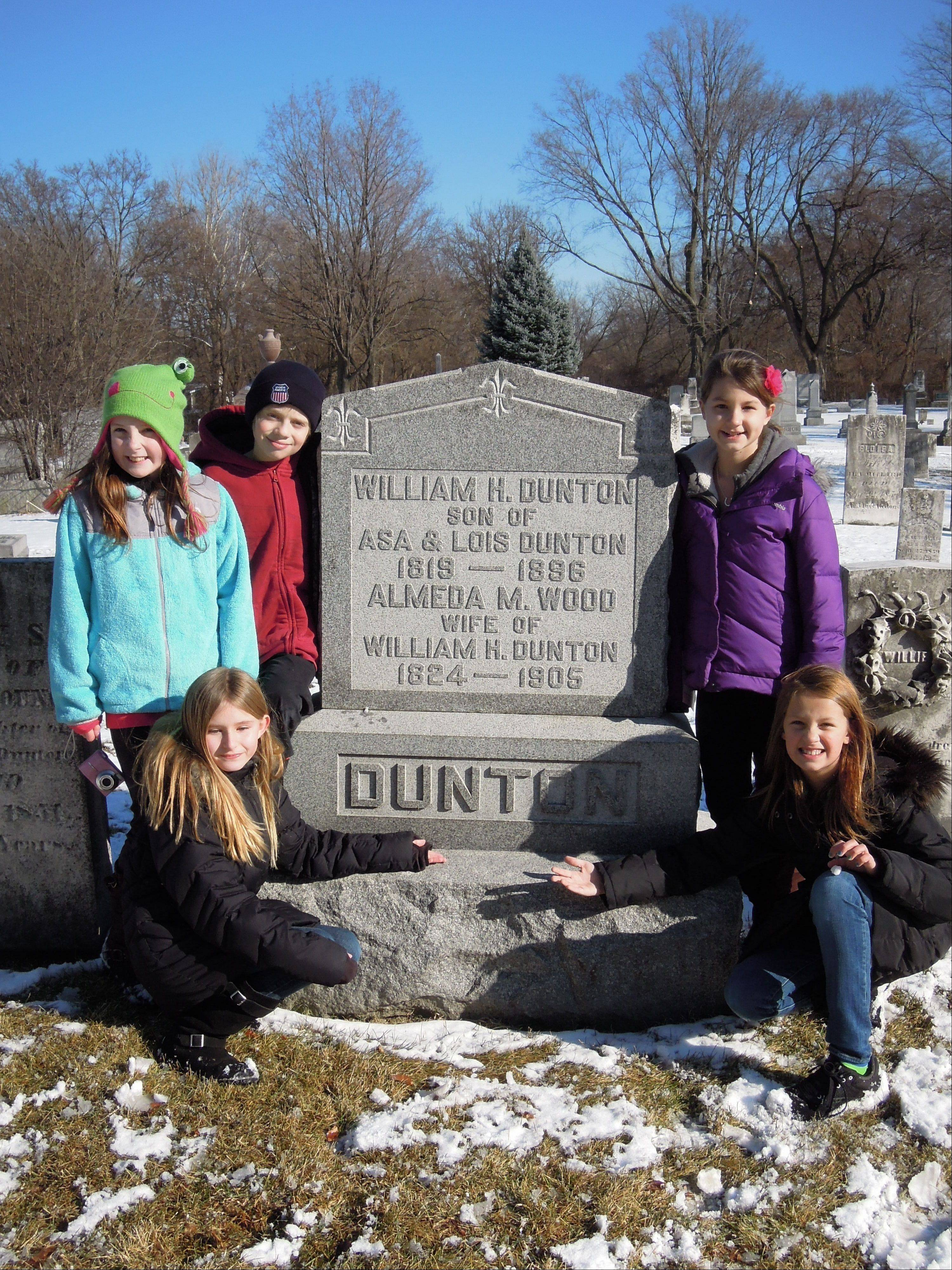 Finding the Dunton family grave are Clara Maki, kneeling on left, with Natalia Lesak and Adam Skzypkowski behind her. Alexandra La Quaglia is on the right with McKenna Kopeny behind.