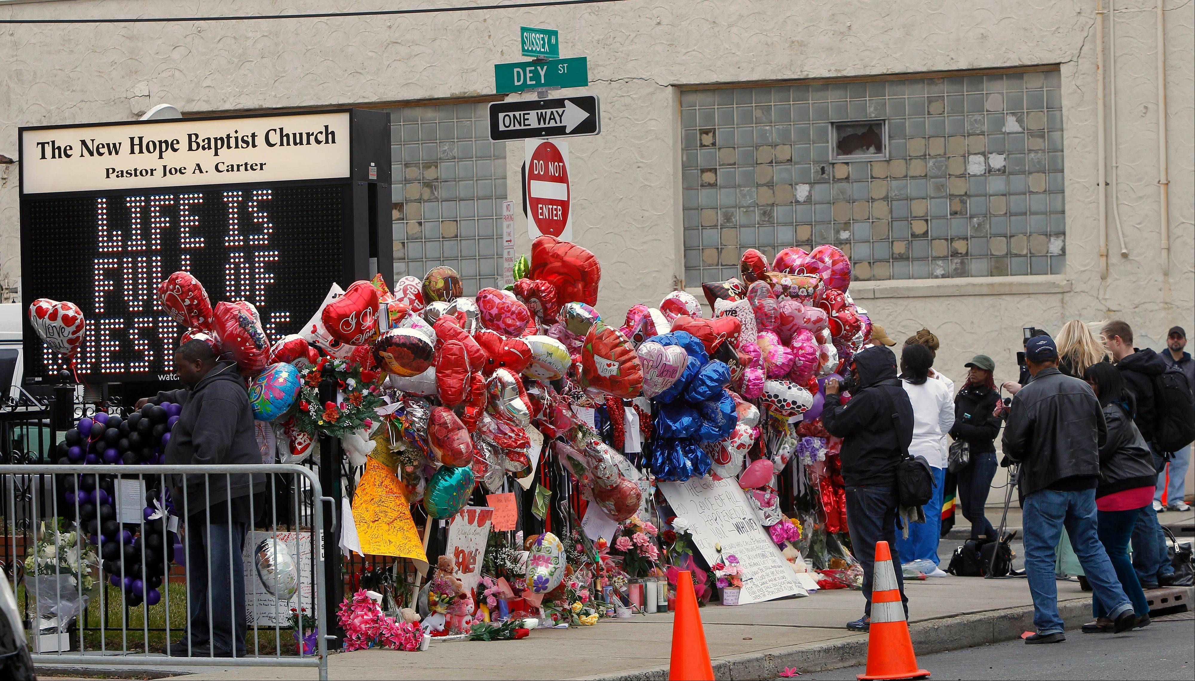 Fans and media surround a makeshift memorial Wednesday as the pay their respects to Whitney Houston at New Hope Baptist Church in Newark, N.J., where her funeral will take place Saturday.