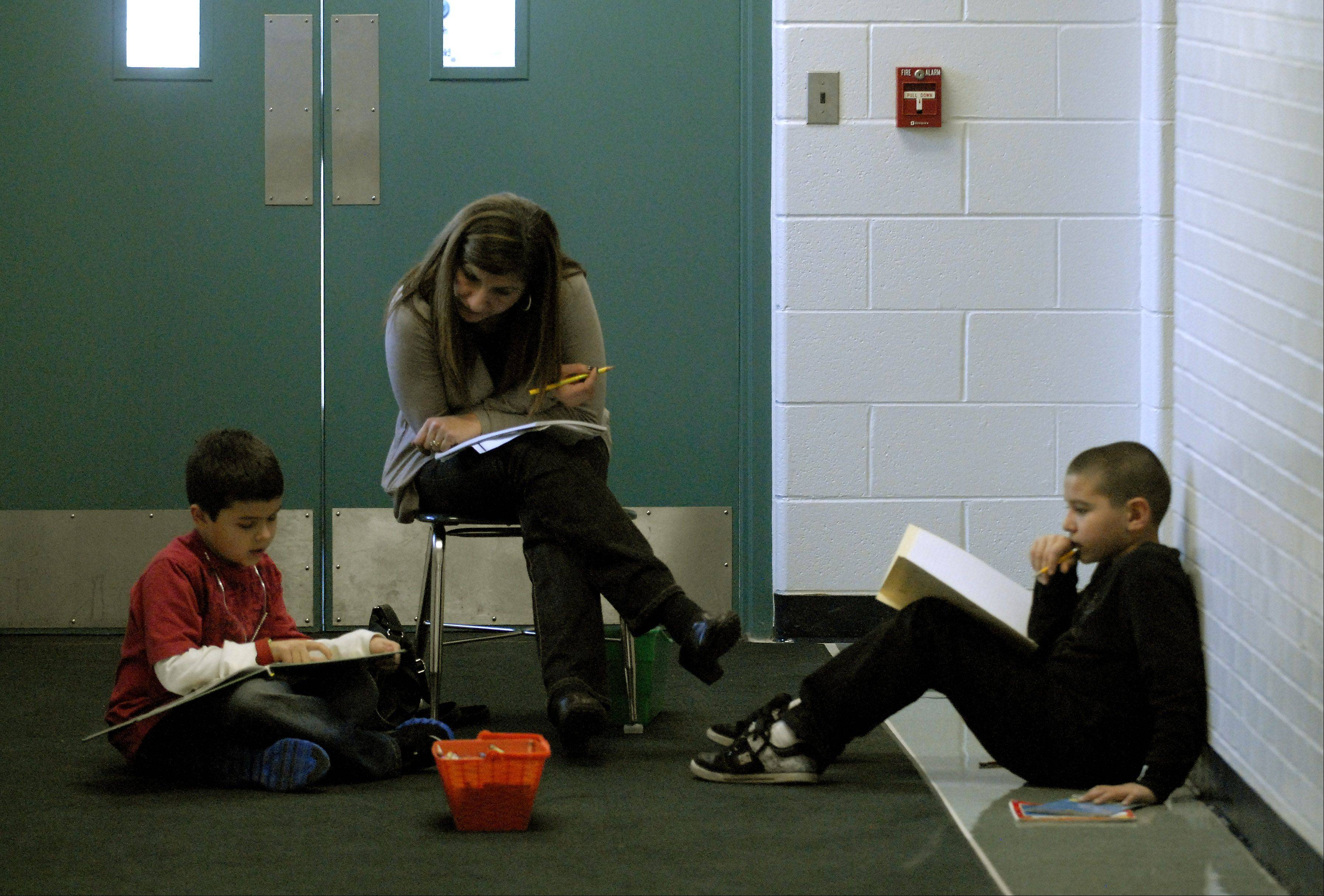 A teacher works with students in the hallway at Robert Frost Elementary School in Mount Prospect. Elk Grove Township Elementary District 59 school board this week voted to build four new classrooms at the school to alleviate overcrowding.