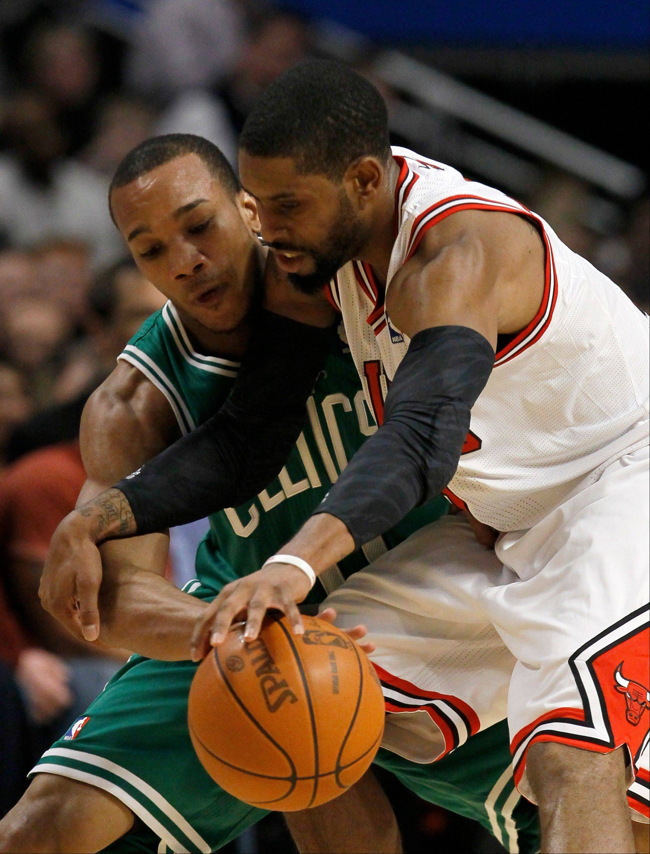 Boston Celtics shooting guard Avery Bradley, left, tries to steal the ball from Bulls point guard C.J. Watson Thursday during the first half.