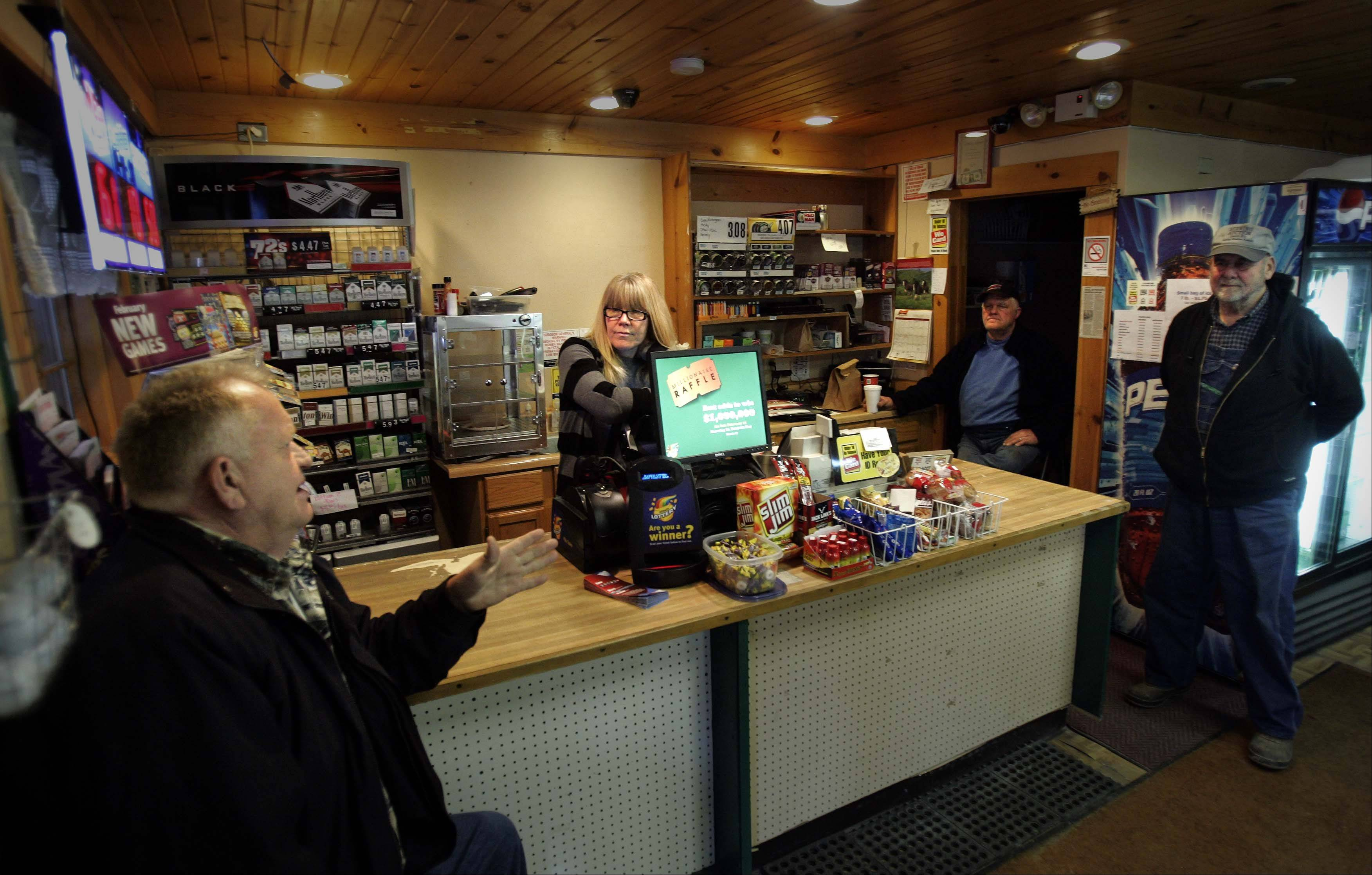 "Cindy Kamijima, center, who runs the General Store of Udina, visits with customers, from left, Erv Glasshagel, of Elgin, Dave Lenox, of Sycamore, and ""Rosey"" Rosenwinkel of Plato Center."
