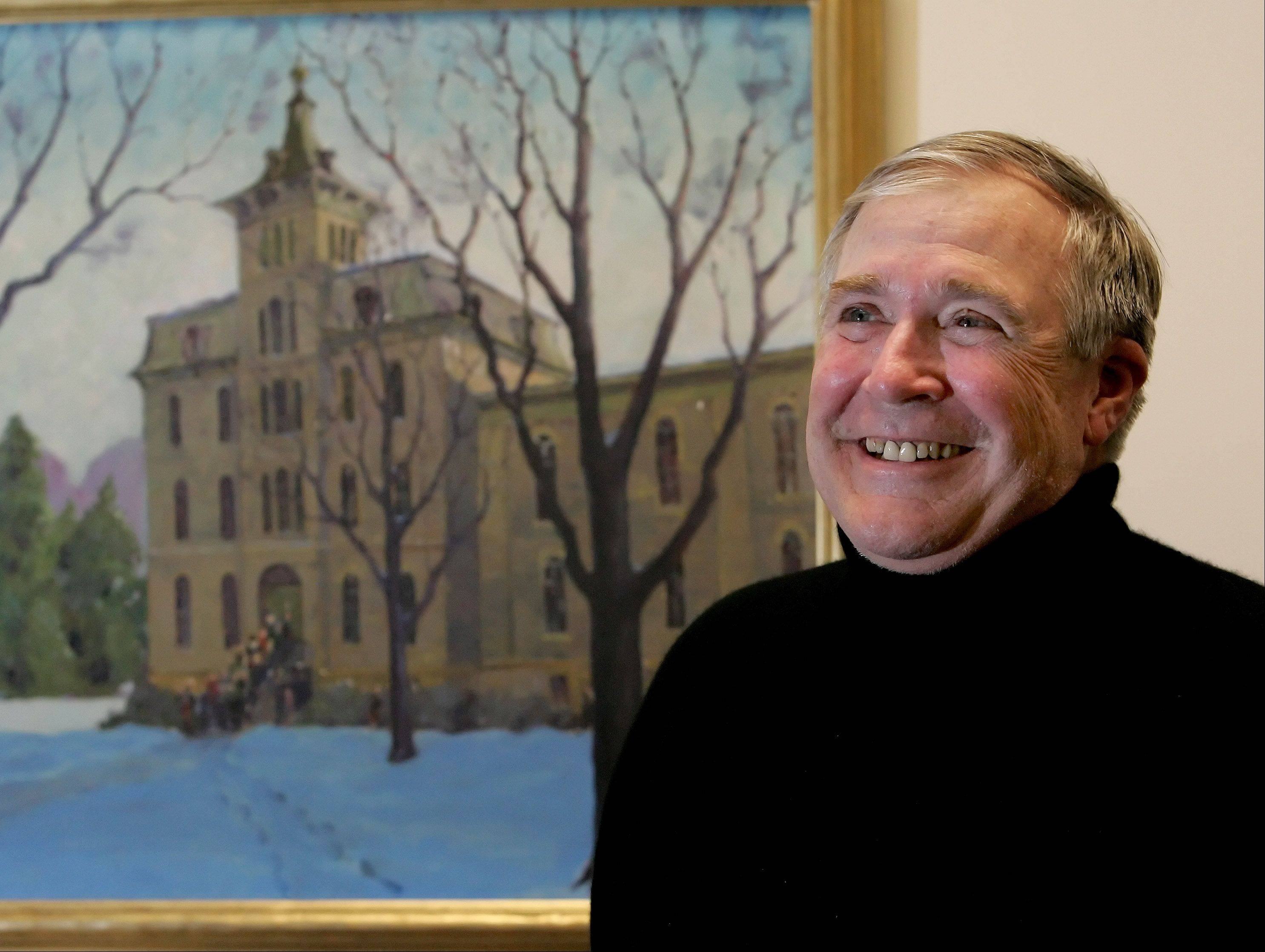 "North Central College President Harold ""Hal"" Wilde pauses in front of a painting of the school's Old Main building."