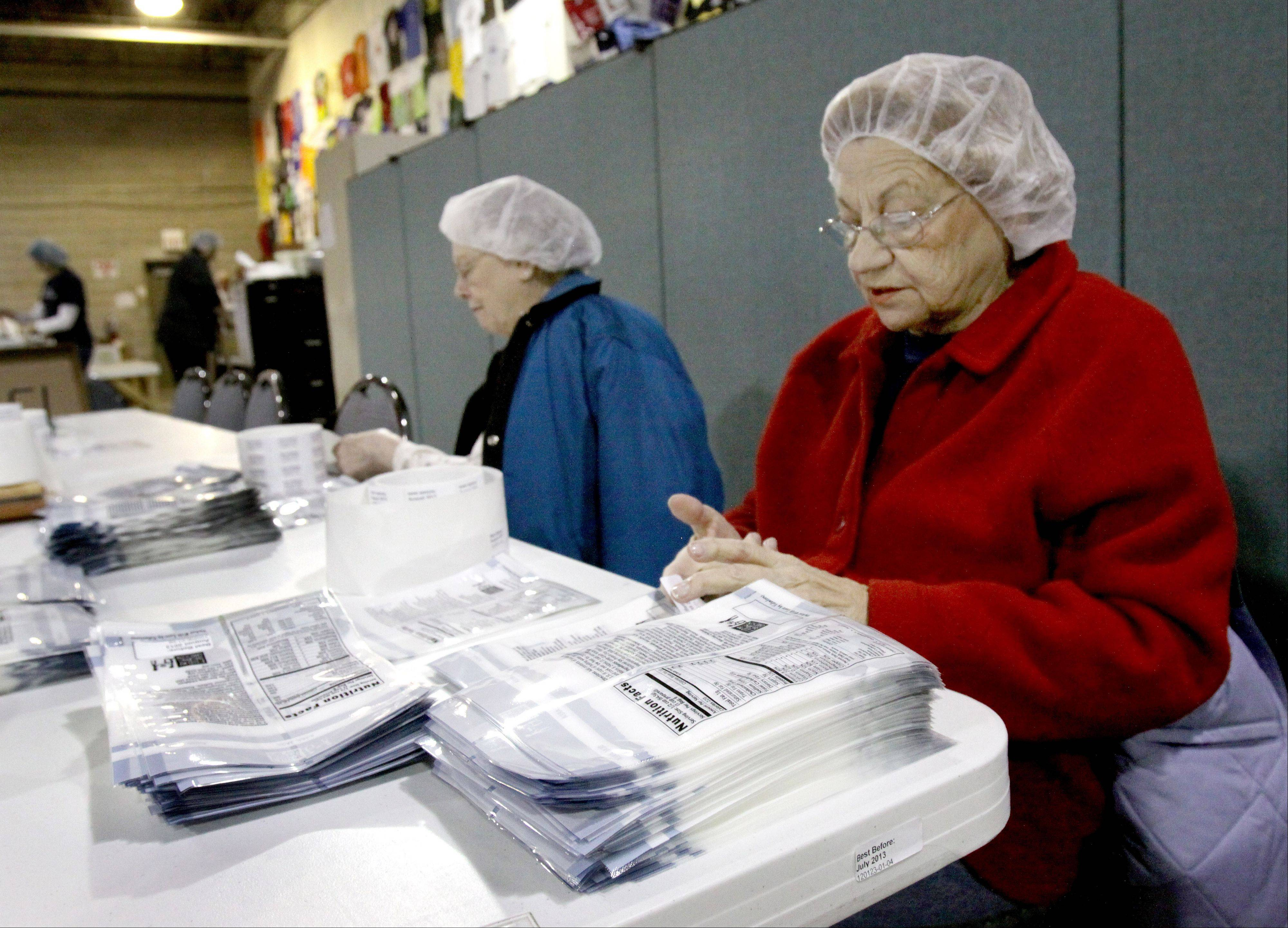 Volunteers Alberta Bergeron, left, and Pat Backer, right, both of Naperville, work at putting expiration dates on bags for meals at Feed My Starving Children in Aurora.
