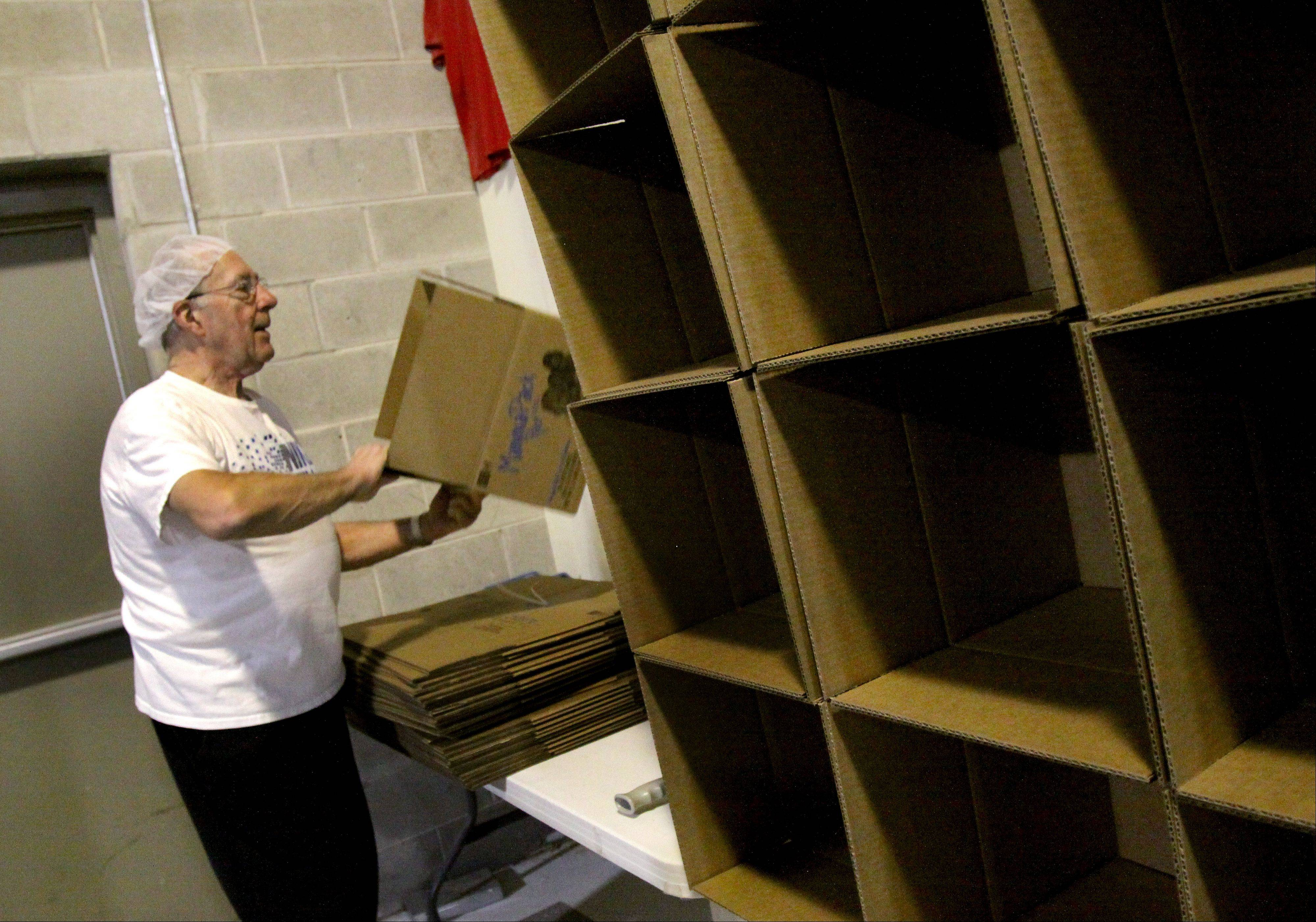 Volunteer Richard Temple of Aurora gets the boxes ready for the food packets.
