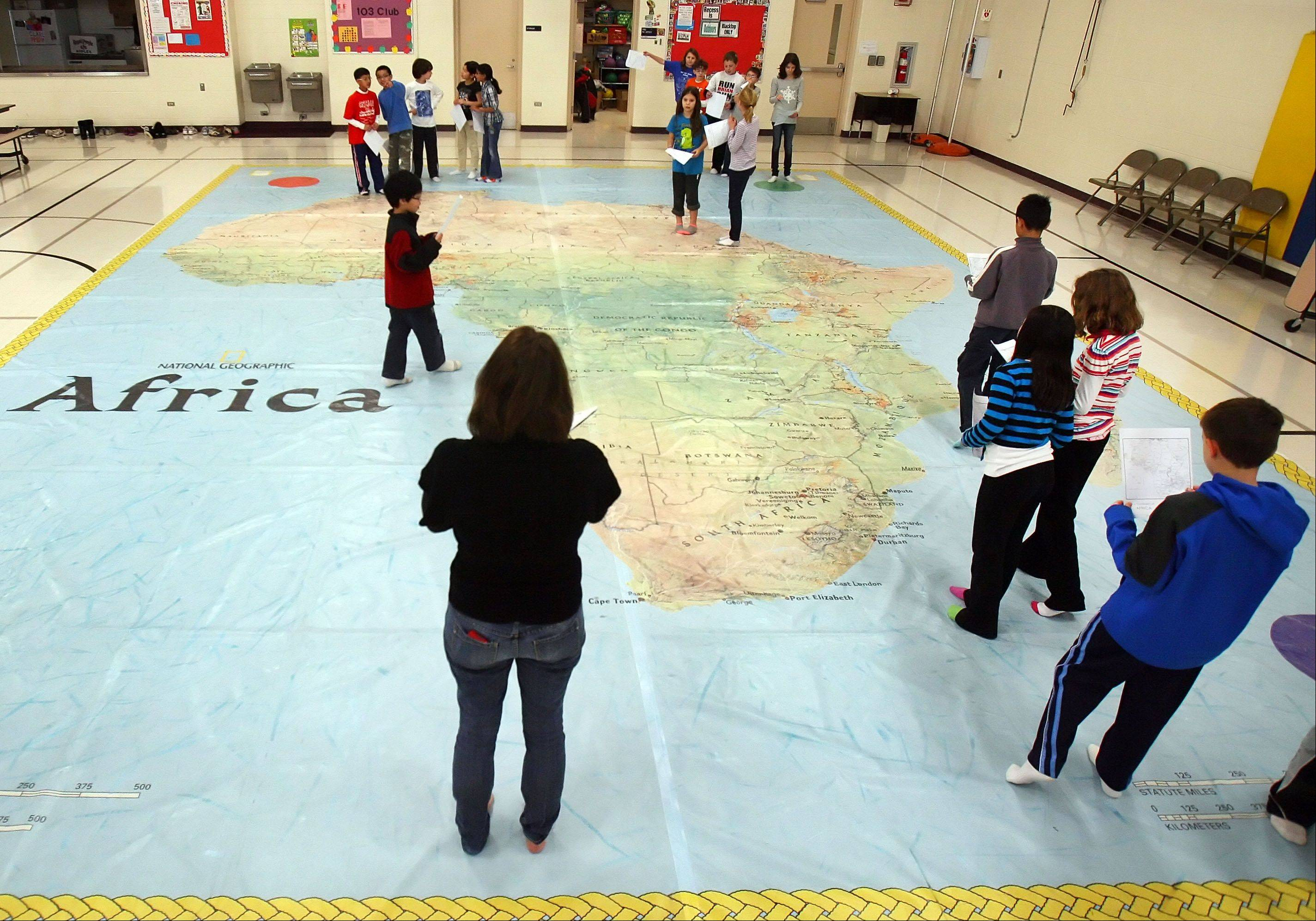 Fourth-grade teacher Kara Fergus leads geography games on a 26-foot-by-35-foot map of Africa at Half Day School in Lincolnshire. The map is part of National Geographic's Giant Traveling Maps program.