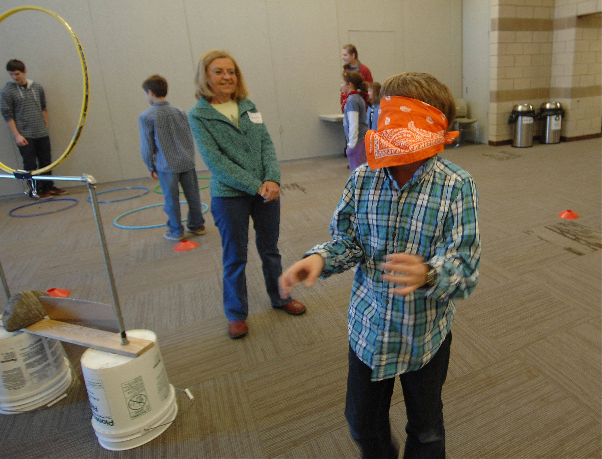 Shawn Costanzi, 9, of Sugar Grove, bumps his way through an activity to learn how to use more than the sense of vision to find objects at the Hickory Knolls Discovery Center in St. Charles Sunday. It was part of an afternoon of events focused on animal groups and activities.