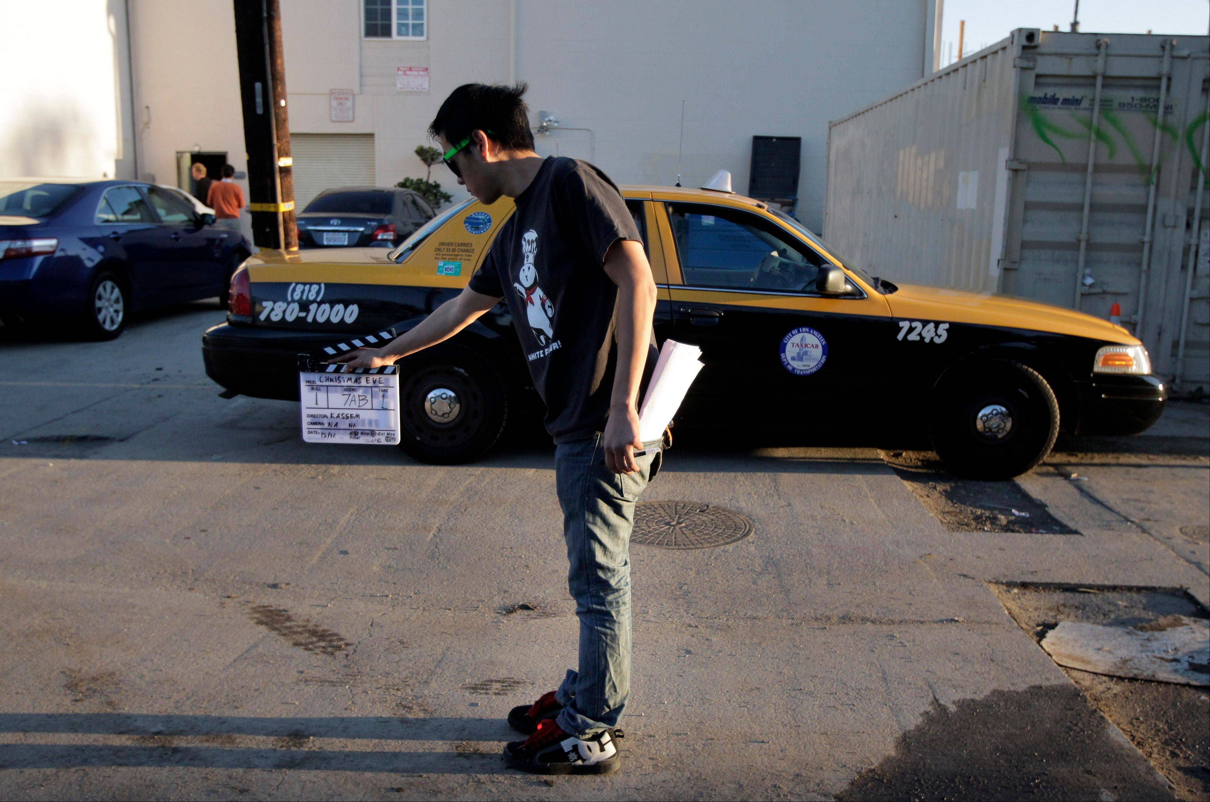 Crew member Arthur Hong holds a clapboard while filming holiday movie trailers at the Maker Studios in Culver City, Calif. The $100 million investment by YouTube in 96 new channels starting in October has sparked a flurry of activity in Hollywood's independent producer community.