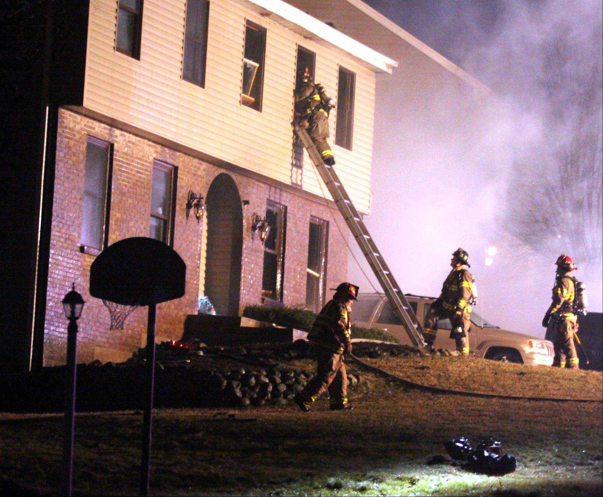 Personnel work at the scene of a fire on the 1100 block of Spring Hill Drive in Algonquin Monday night.