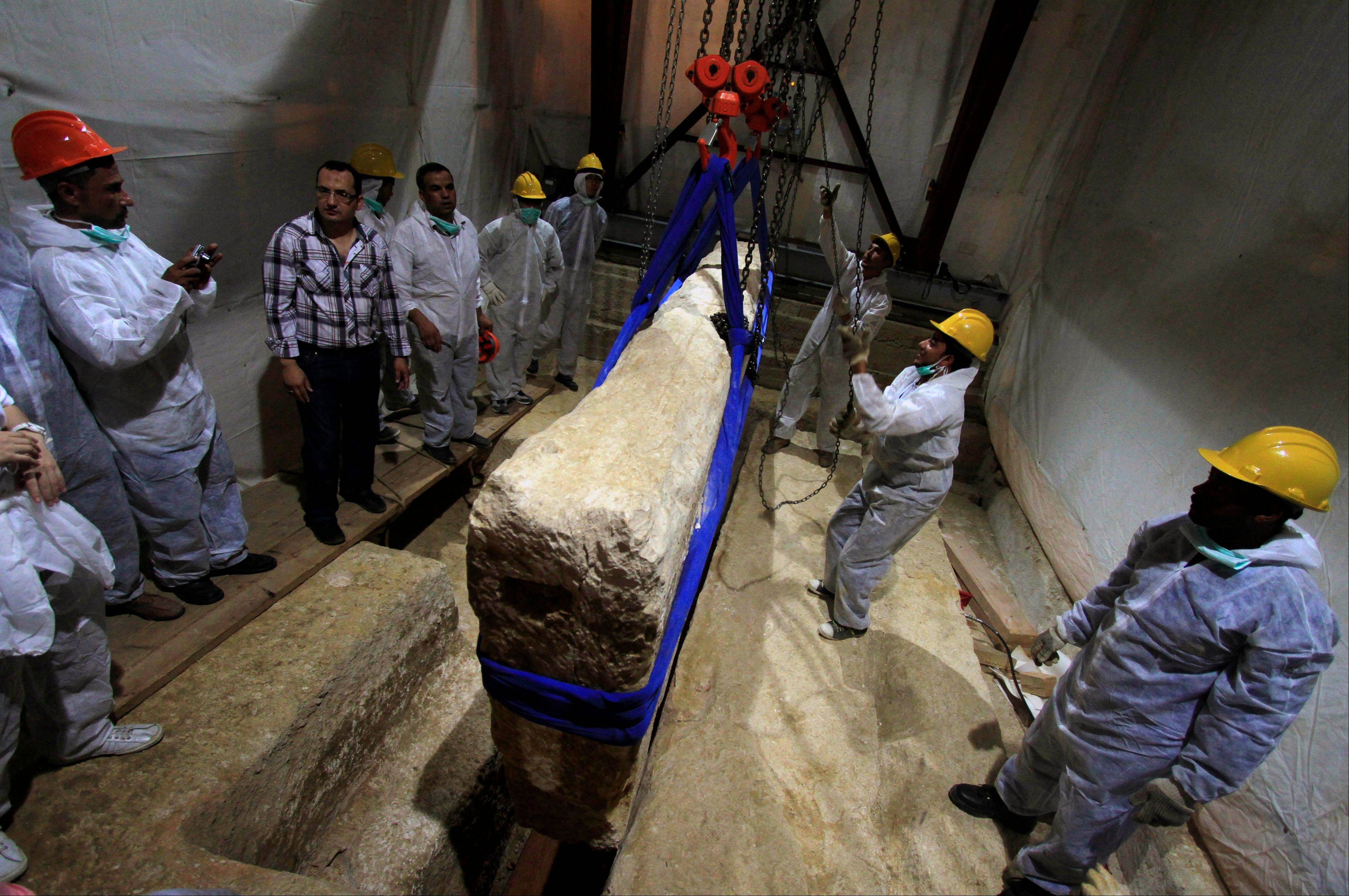 In this Thursday, June 23, 2011 file photo, an Egyptian and Japanese team of scientists use a pulley system to lift the first of 41 16-ton limestone slabs to reveal fragments of the ancient ship of King Khufu next to the Great Pyramid of Giza, Egypt. Archaeologists began a second-phase of restoration work on a 4,500-year-old wooden boat found next to the Great Pyramid of Giza, one of Egypt's main tourist attractions.