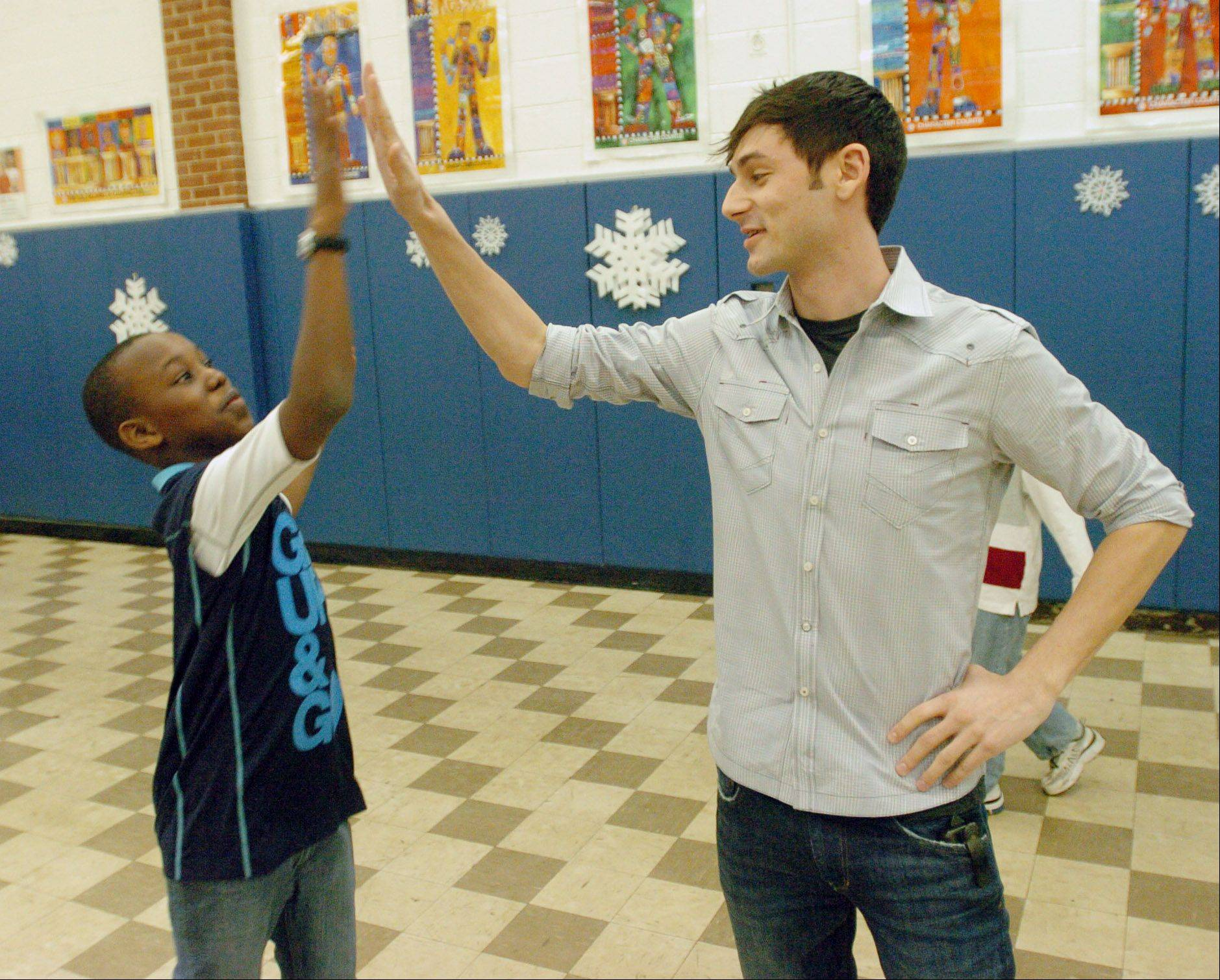 "Mike Gianatasio Recreation Program Manager at the Lisle Park District gives Martin Bandzoumouna, 12, of Lisle a high-five at the after-school program at Schiesher School in Lisle Wednesday. Gianatasio is credited for doubling the enrollment of the ""No Name Teen Camp."""