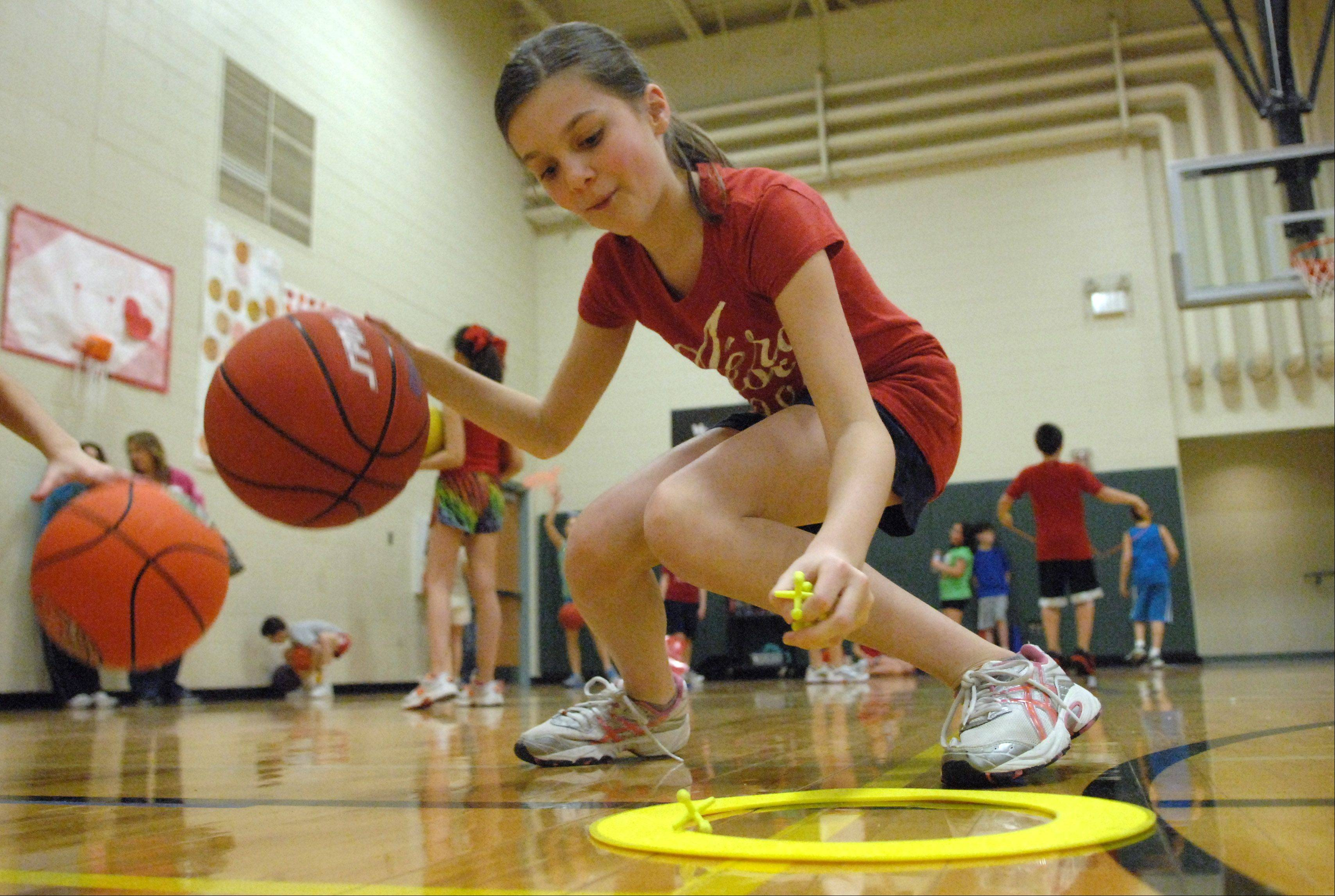 5th-grader Madison Overly has to dribble a basketball with one hand while scooping up jacks with the other as kids at Martin Elementary School in Lake in the Hills take part in Hoops for Hearts Thursday. Hoops For Heart is a national fundraising program that promotes physical activity, heart healthy living, and community service to children.