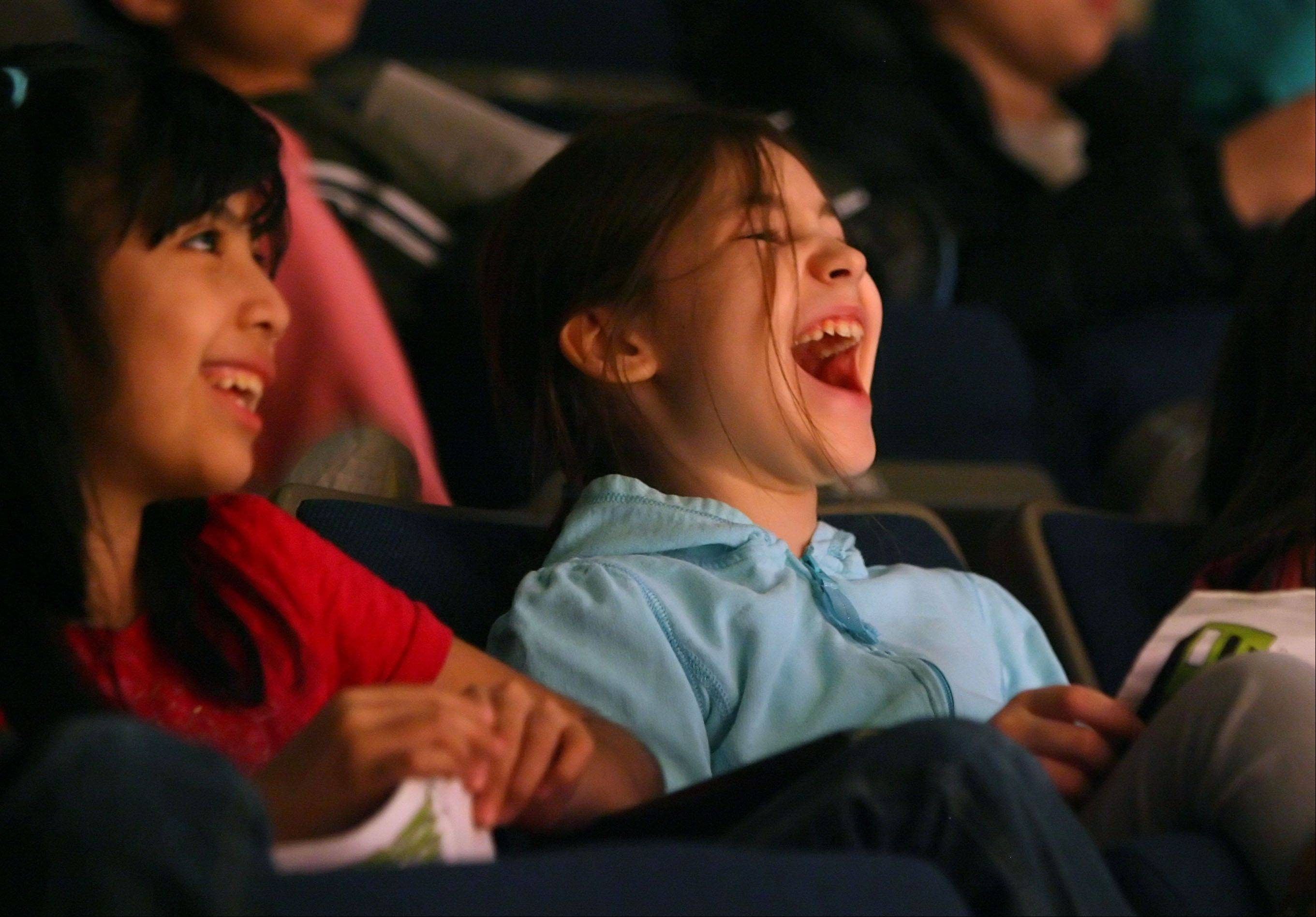"Hawthorn Elementary North students 9-year-old Yasmin Makos, left, and 8-year-old Deborah Damianov watch the Vernon Hills High School production of ""Sideways Stories from Wayside School"" during a winter matinee Friday in Vernon Hills."
