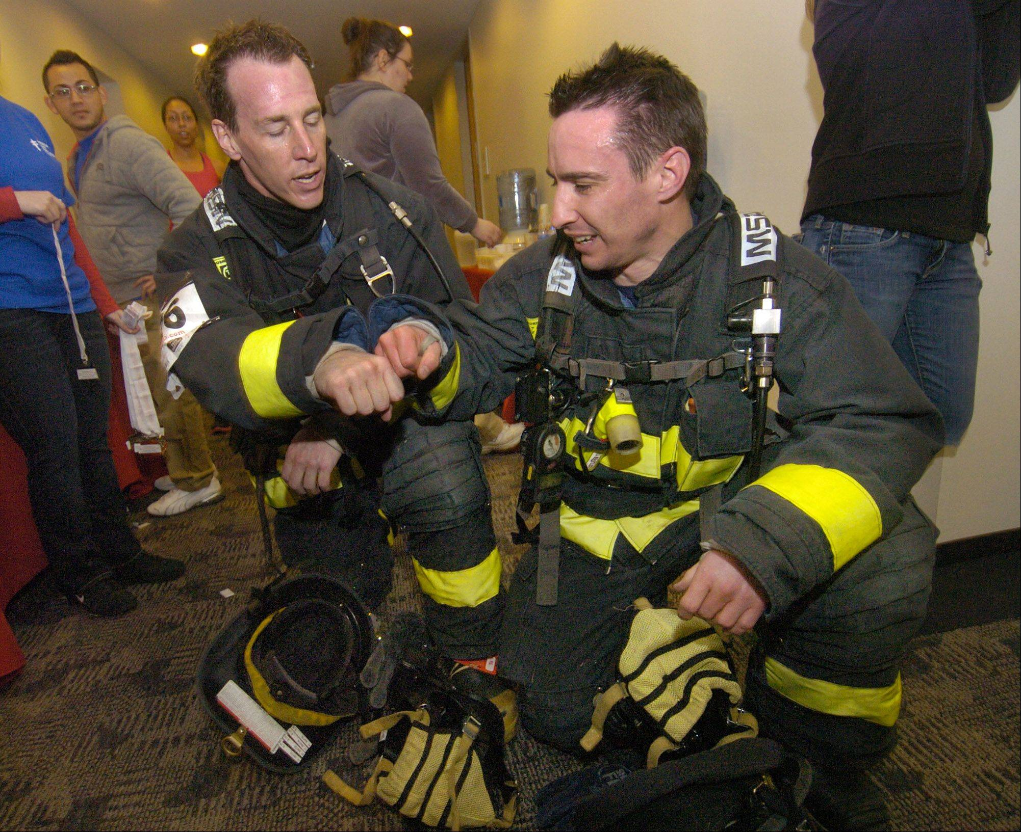 Glen Ellyn firefighters John Martin and Warren Rickert congratulate themselves after climbing the 31 stairs in full equipment at the Greater Chicago Fight For Air Climb at the Oakbrook Terrace Tower.