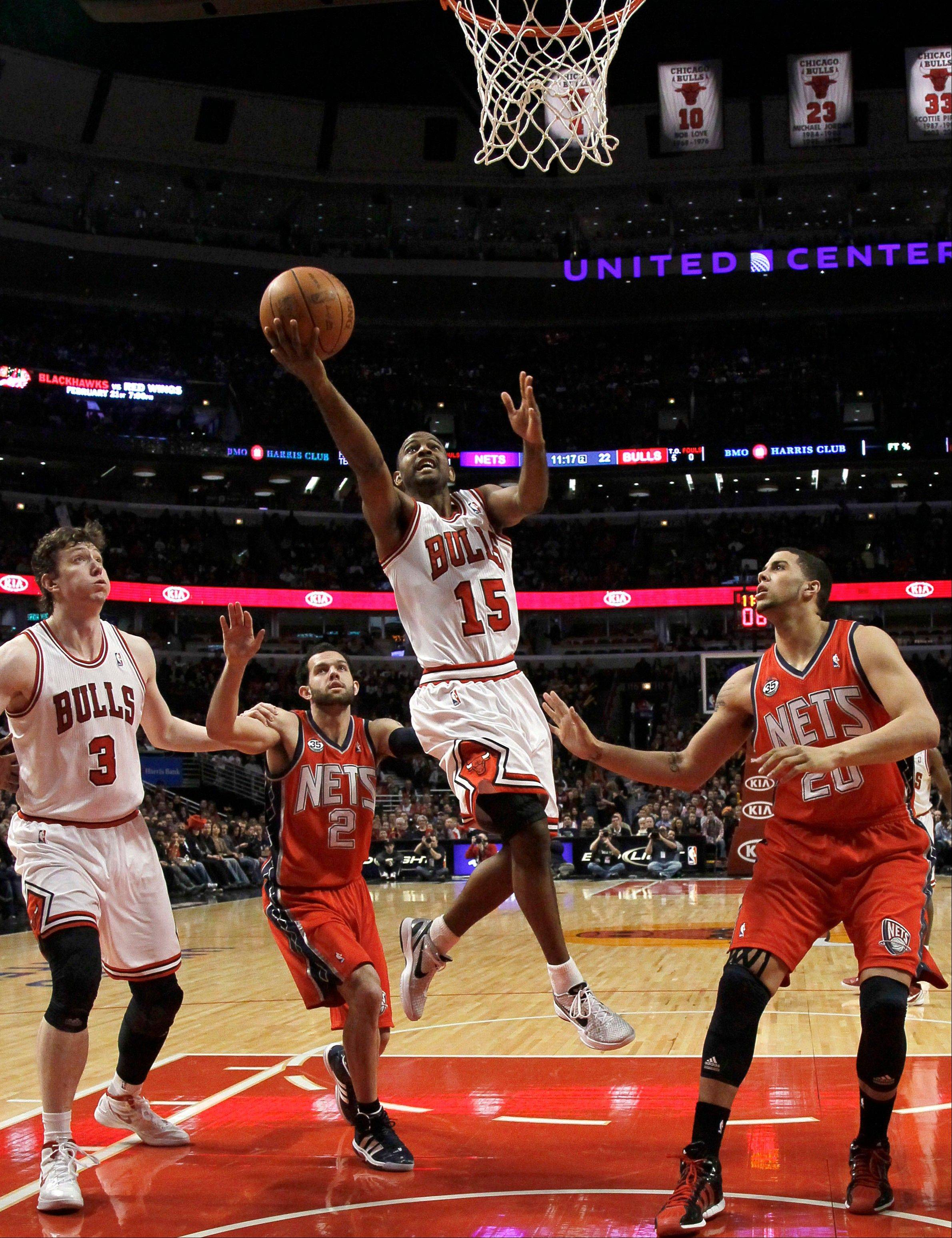 Chicago Bulls guard John Lucas (15) shoots to score past New Jersey Nets point guard Jordan Farmar (2) and Jordan Williams (20) as Bulls' Omer Asik (3) watches the play Saturday during the first half in Chicago.
