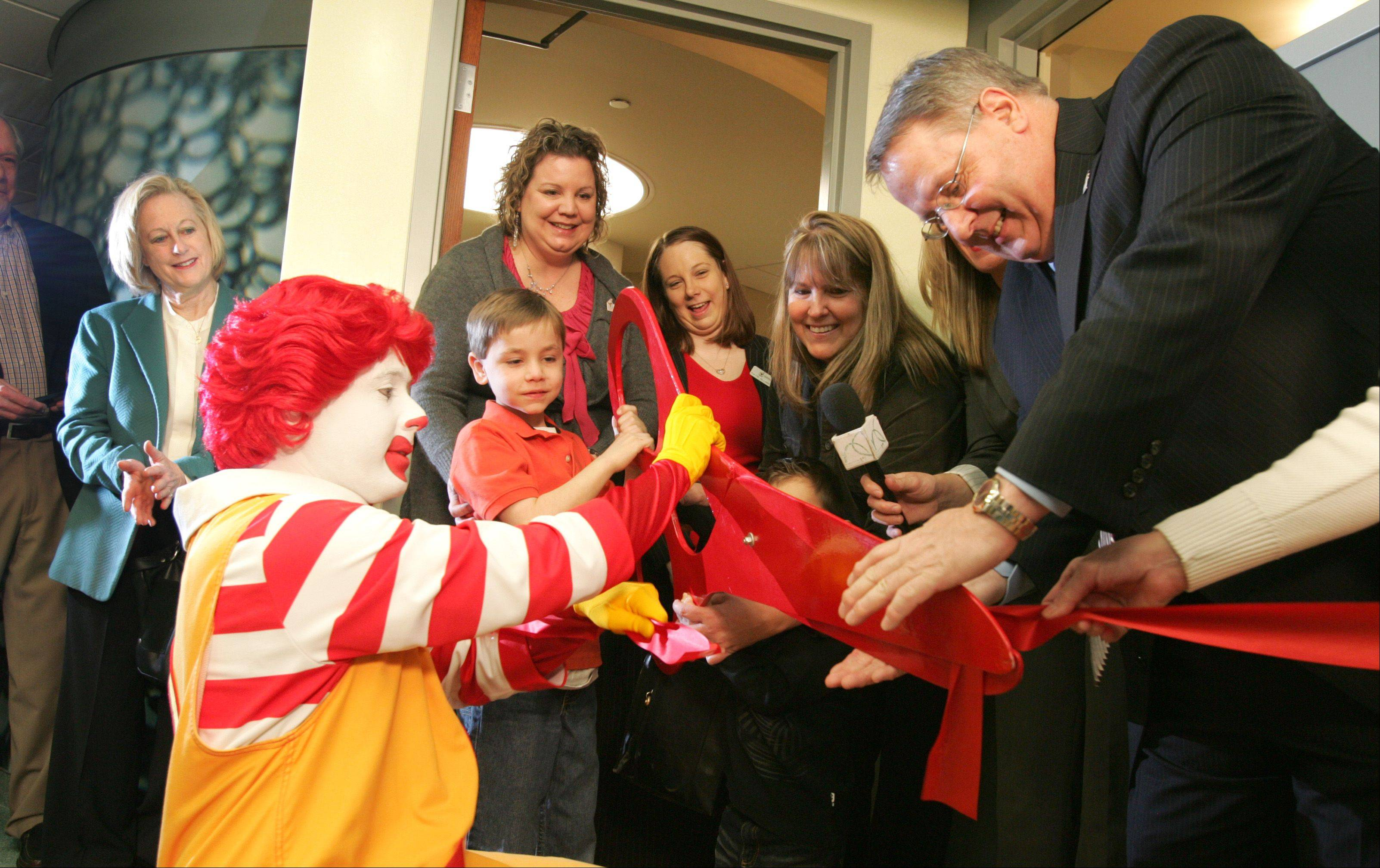 Ronald McDonald cuts a red ribbon at the unveiling of the Ronald McDonald Family Room in Edward Hospital. At right, Doug Porter, CEO of Ronald McDonald House Charities of Chicagoland and Northwest Indiana, assists.