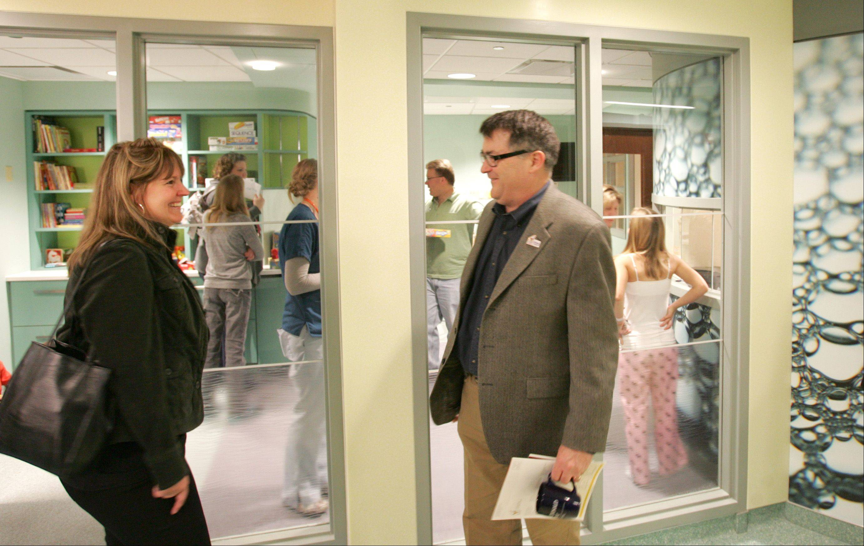 Keri Gillespie and Dr. Bob Covert, right, medical director of Edward's Newborn Intensive Care Unit, chat inside the playroom in the Ronald McDonald Family Room.