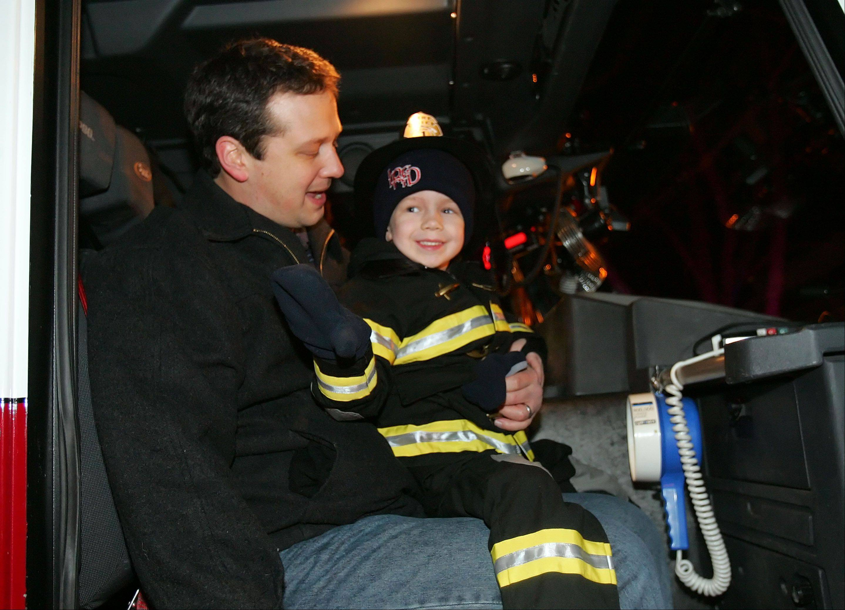 Four-year-old Connor Johnson of Libertyville waves to family members and friends as he gets ready for a ride on a fire truck with his father, Mike Johnson, Monday night in Libertyville. Firefighters and police officers from a dozen or more jurisdictions were on a special call, a grand show of support for Connor, who suffers from an aggressive and rare form of brain cancer.